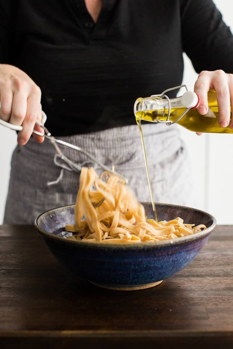 Tossing homemade pasta with olive oil