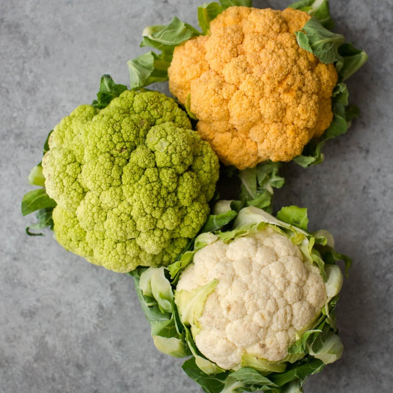 Overhead shot of orange, green, and white cauliflower heads.