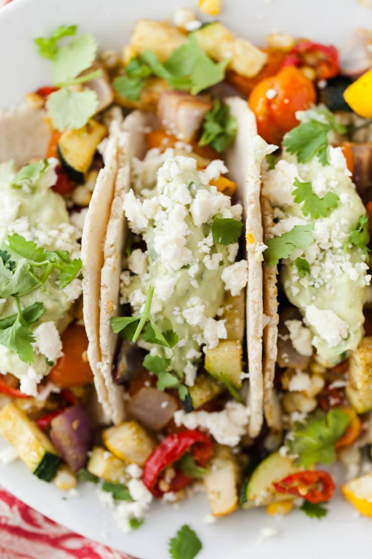 Close-up, overhead photo of tacos on a white plate, loaded with roasted summer vegetables, an avocado cream, and a sprinkle of feta.