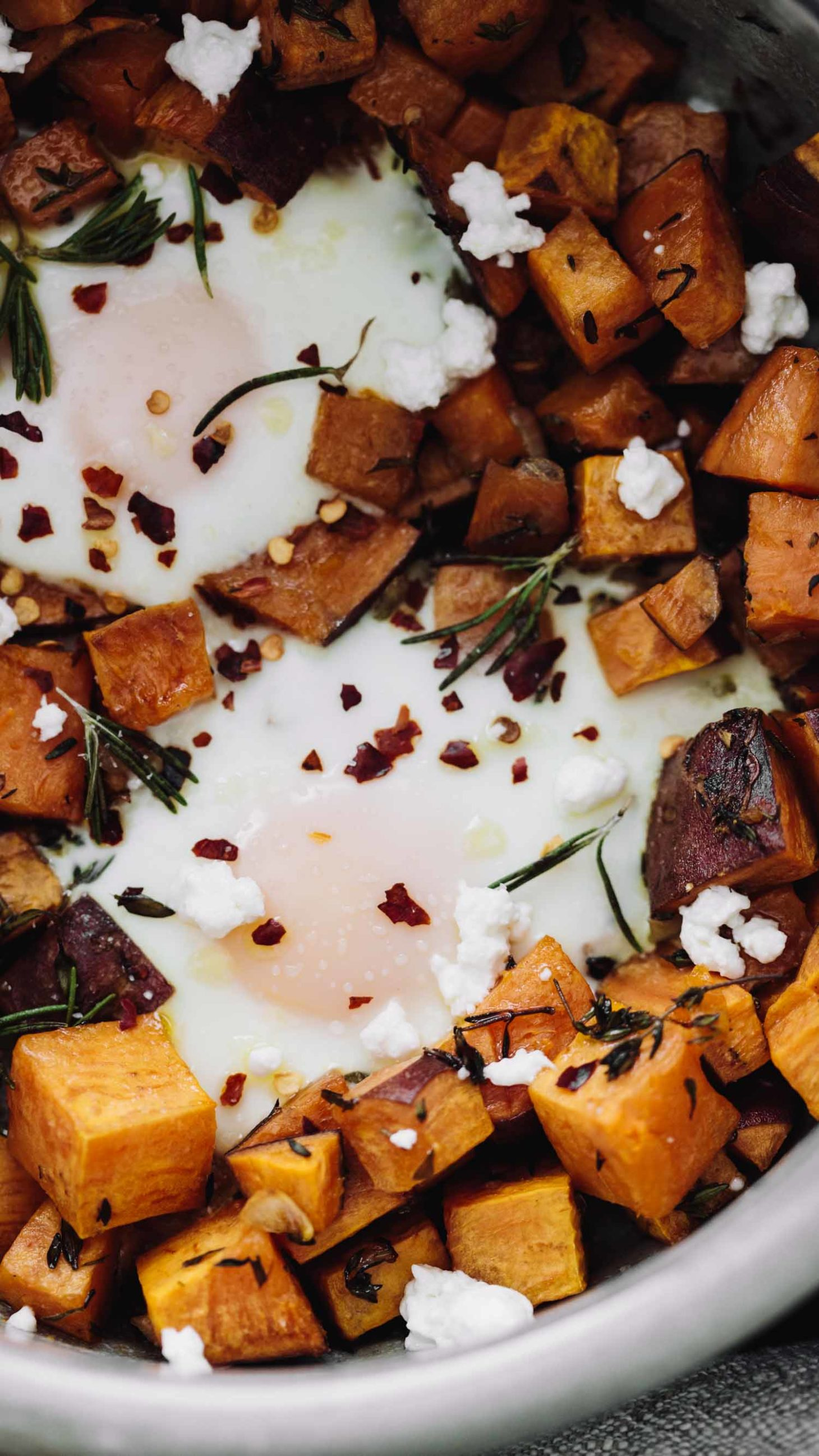 Close-up, overhead photo of roasted sweet potatoes with baked eggs nestled in among the sweet potatoes.