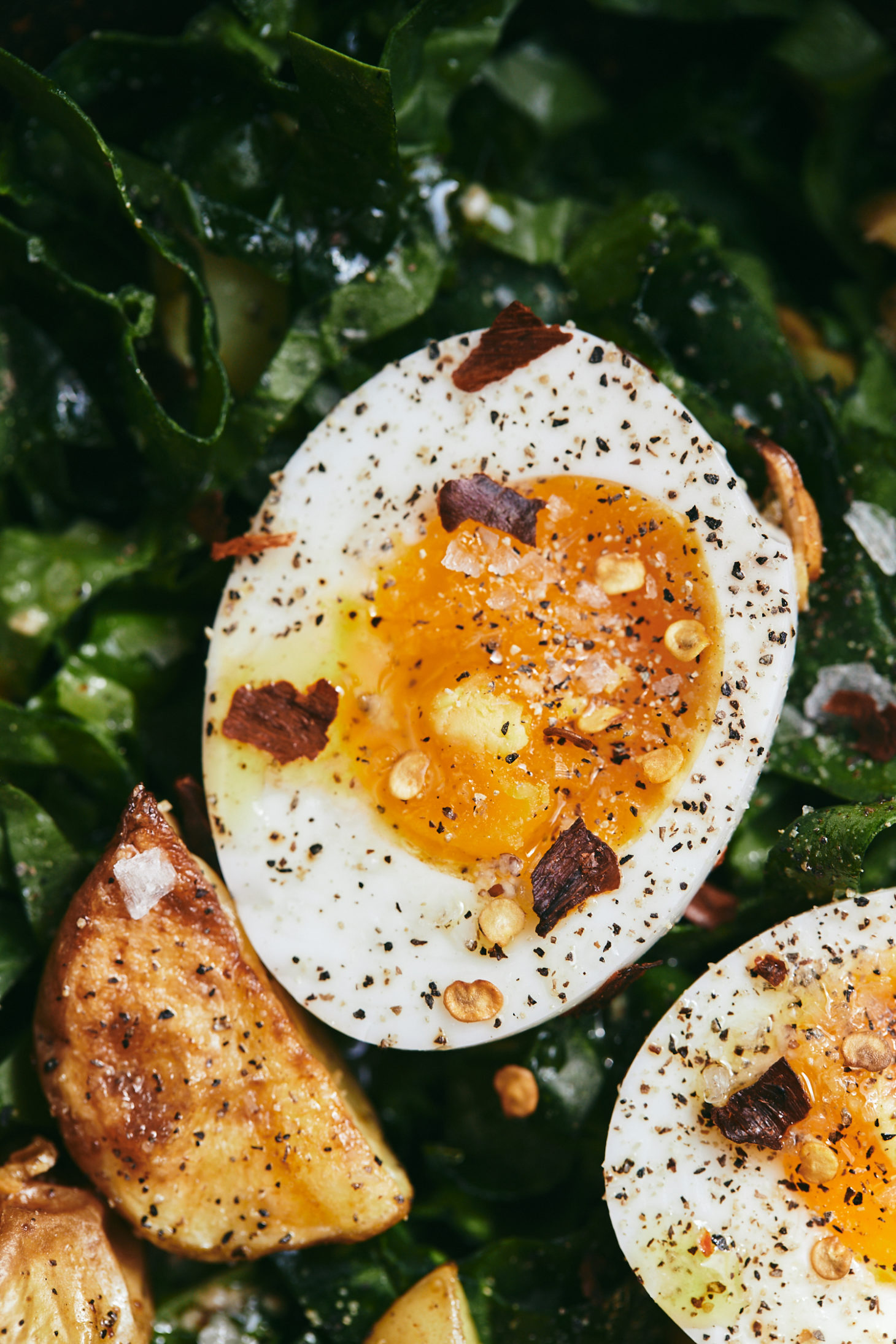 Close-up Overhead photograph of a spinach salad topped with roasted potato wedges and soft-boiled eggs.