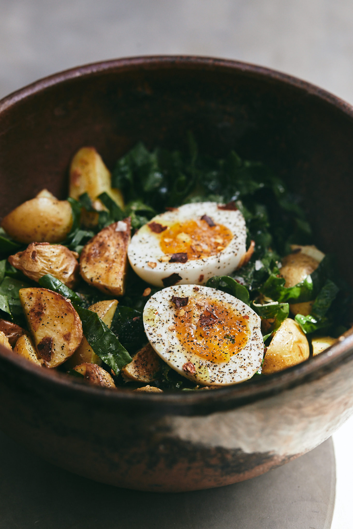Side-angle photograph of a spinach salad topped with roasted potato wedges and soft-boiled eggs.