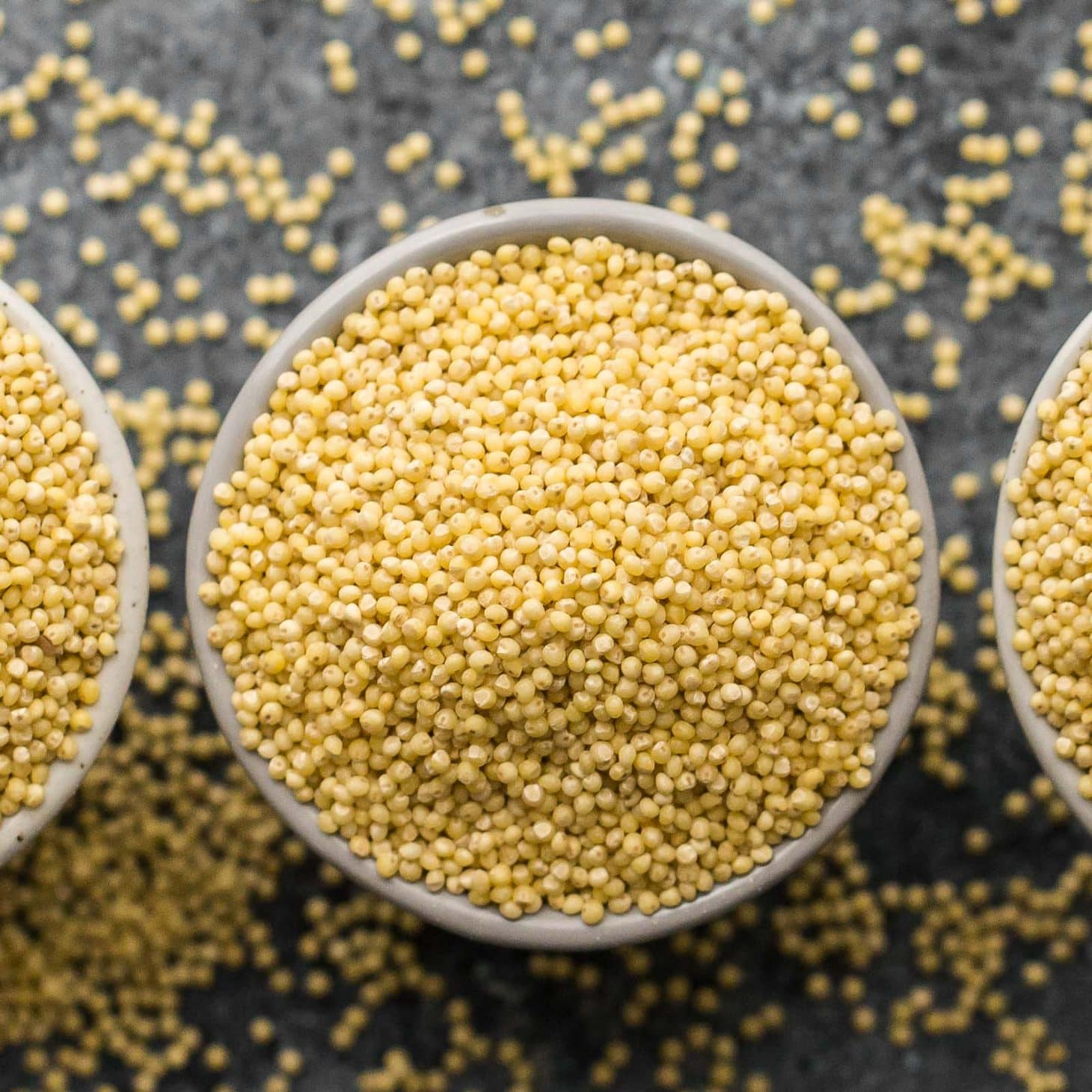 side-angle photo of cooked millet being spooned out of a stainless steel pot-ready to use in millet recipes