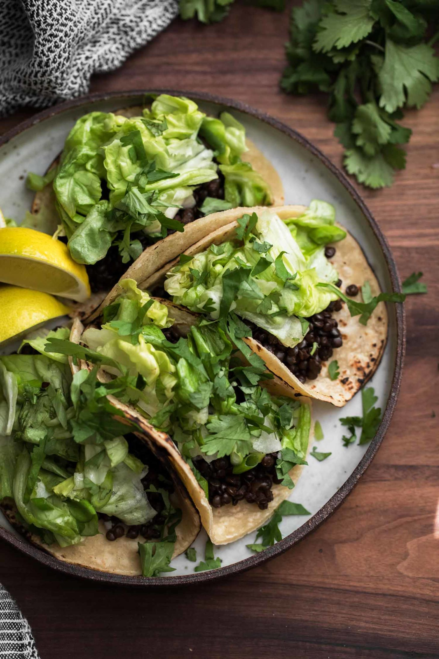 Overhead shot of vegan tacos stuffed with chipotle lentils and a lightly dressed butter lettuce salad.