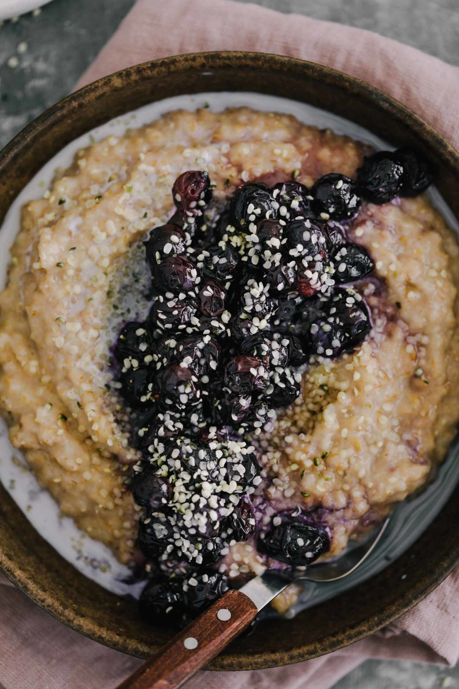 Overhead shot of cracked spelt porridge topped with roasted blueberries and hemp seeds