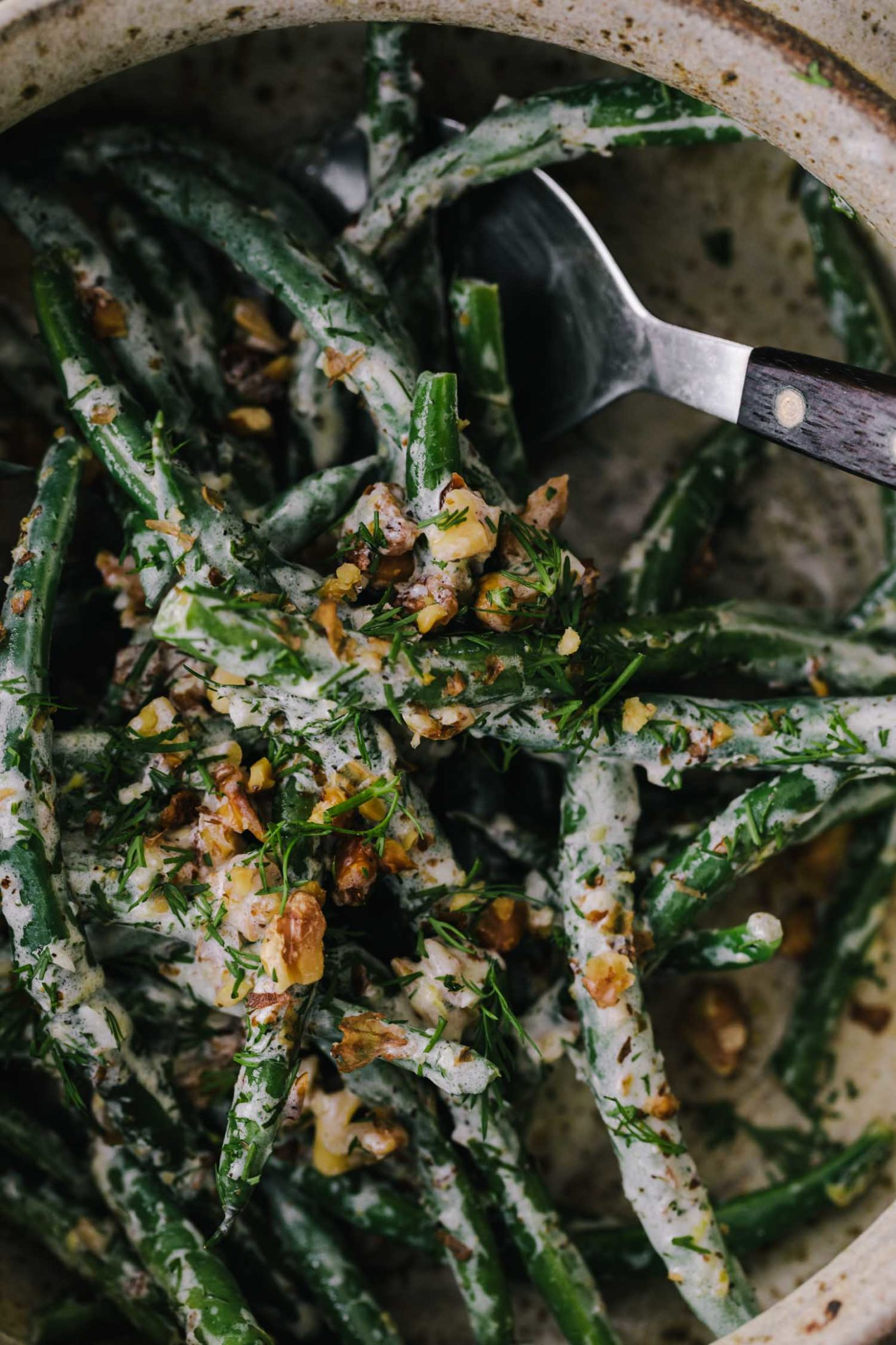 Side Angle Photo of yogurt green beans that have been blanched and tossed with walnuts and yogurt sauce.