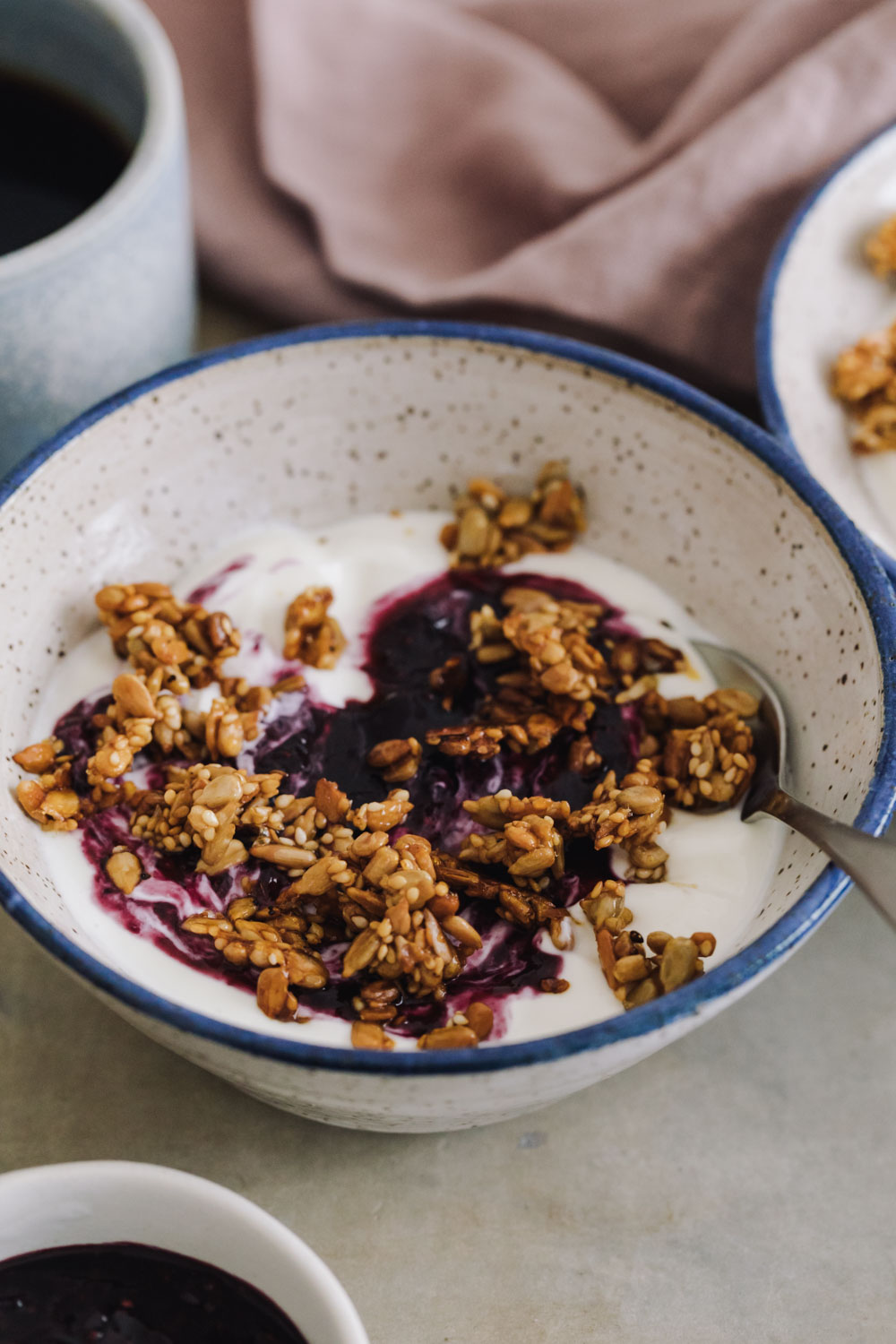 Close-up side angle of yogurt topped with blueberry chia jam and granola