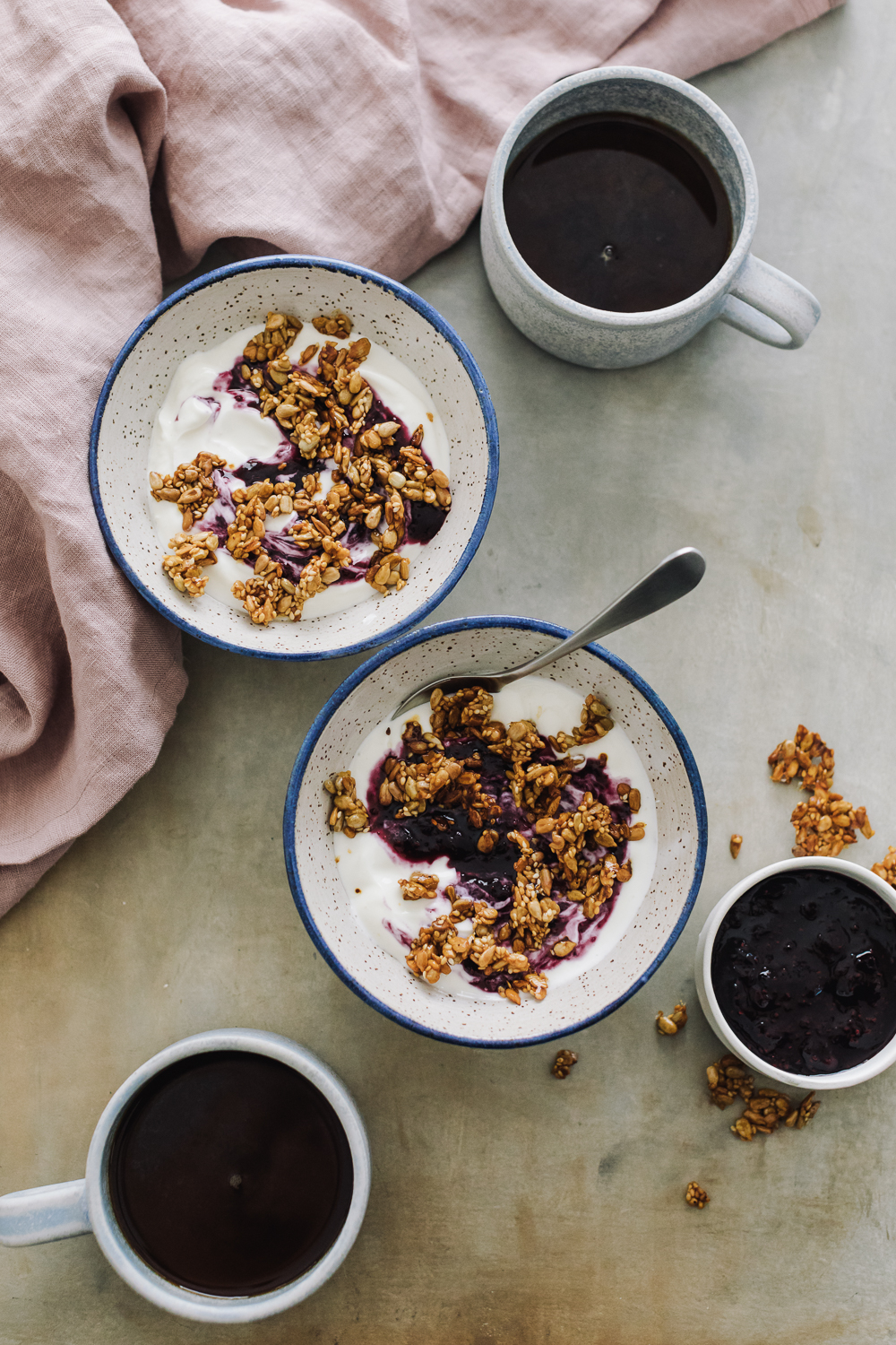 Overhead shot yogurt topped with blueberry jam and granola with cups of coffee and a pink linen.