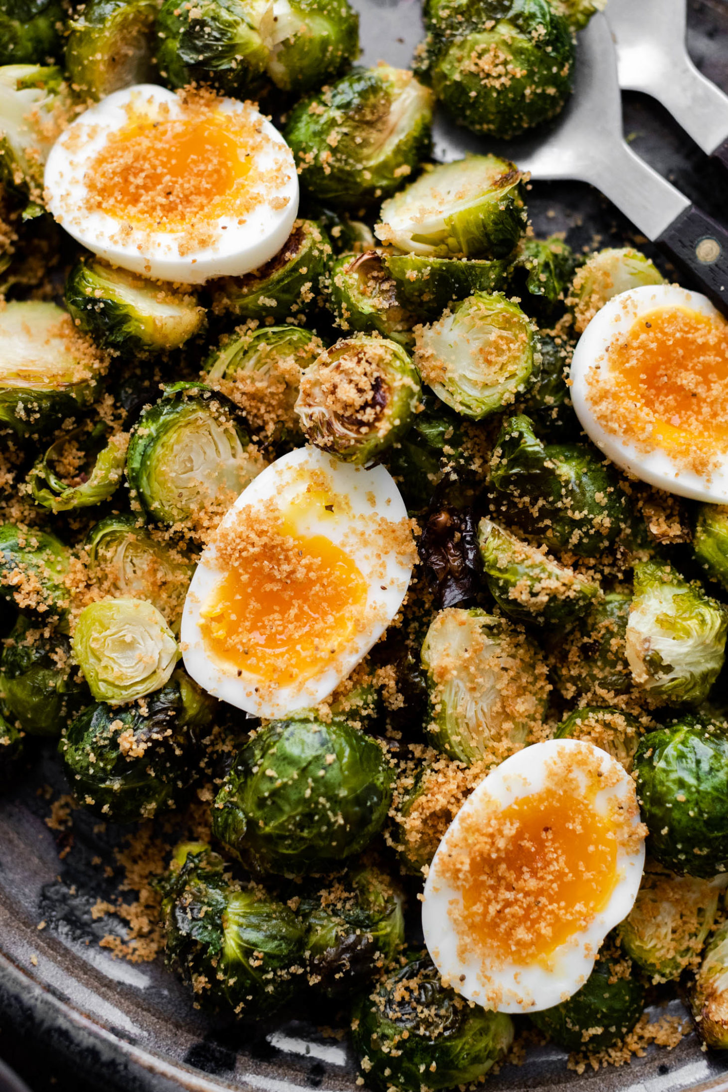 Close-up overhead shot of roasted Brussels sprouts and soft-boiled eggs