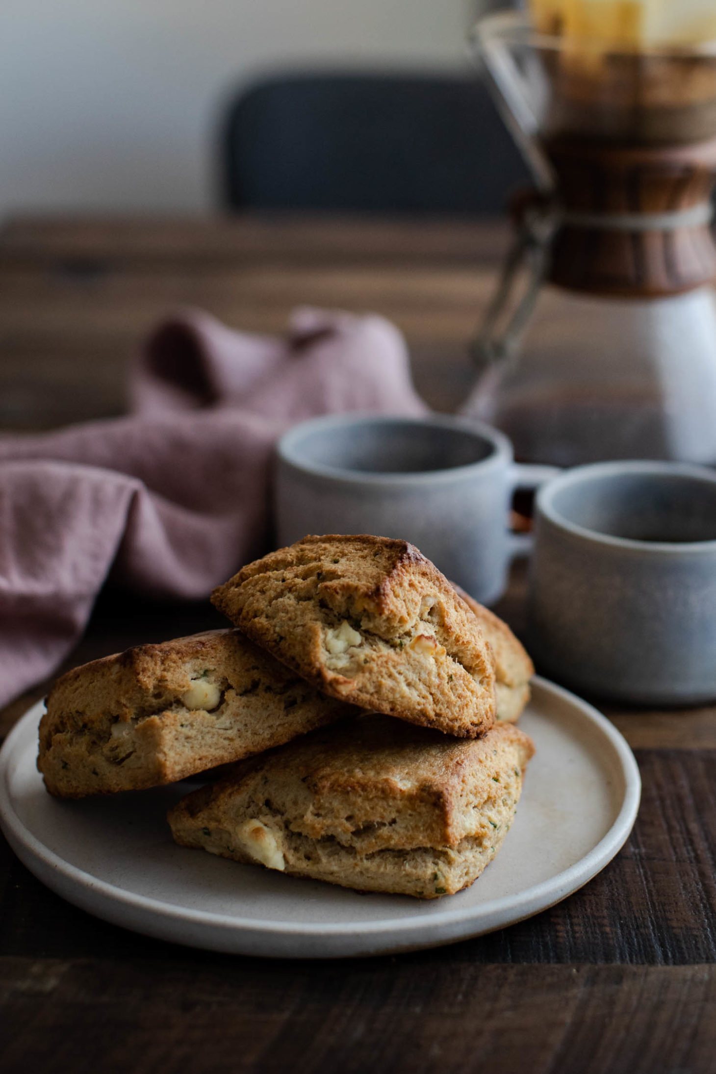 Side angle photo of golden, savory scones filled with feta and chives with blue coffee mugs and chemex in the background.
