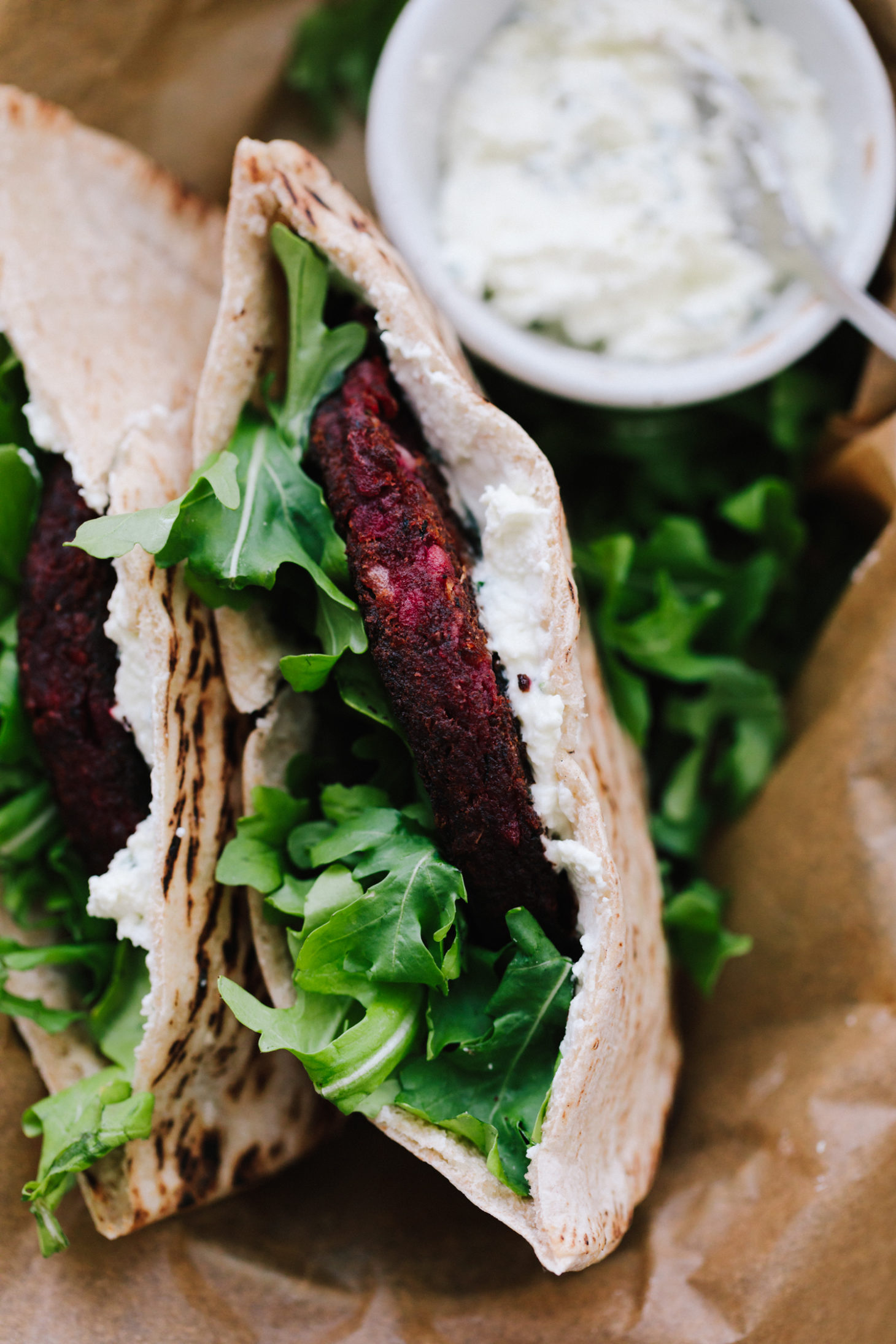 Close-up, overhead shot of pita stuffed with beet burgers, arugula, and whipped feta