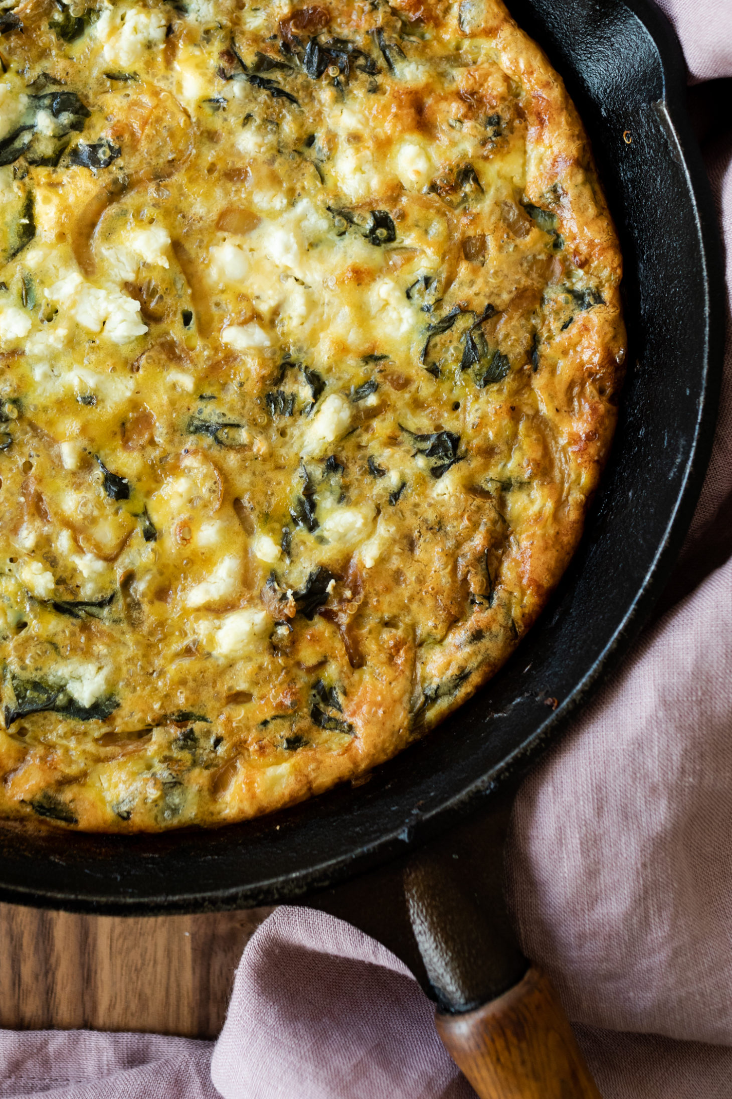 Close-up overhead shot of a chard frittata in a black cast iron pan with a pink napkin.