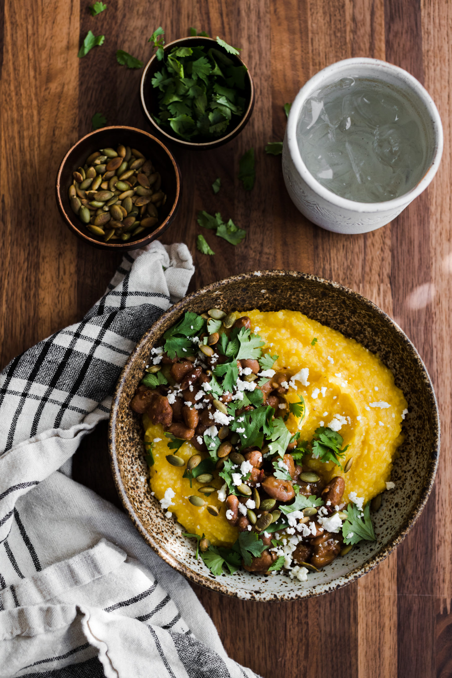Overhead photo of pumpkin polenta topped with pinto beans, pepitas, and feta.