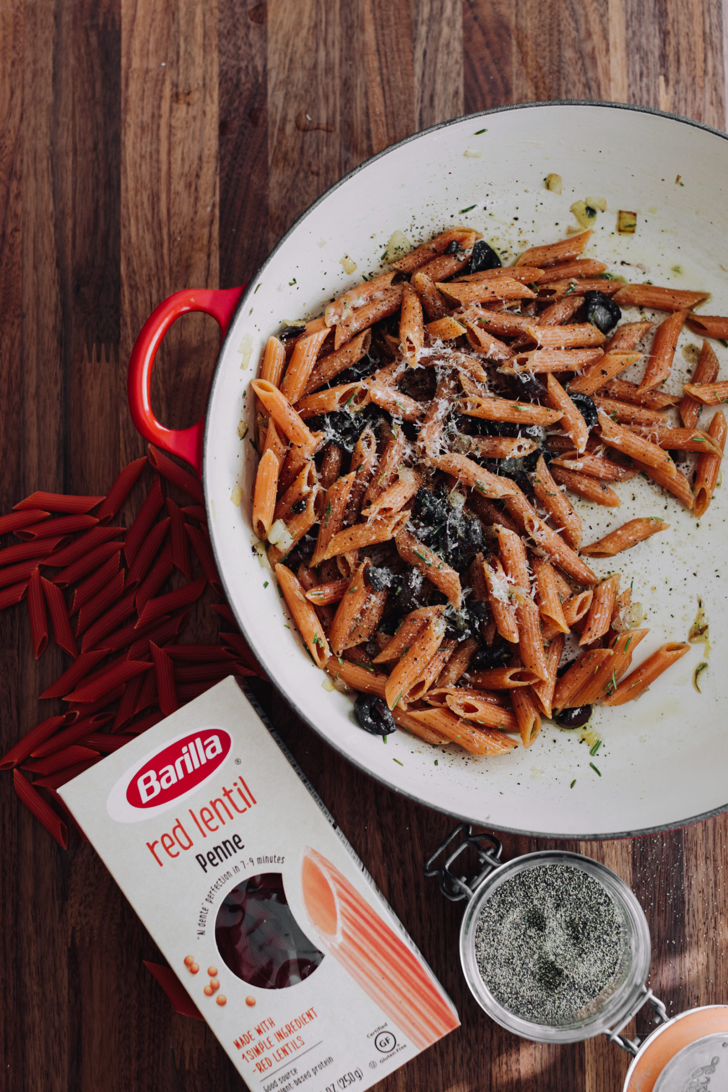 Overhead photograph of red lentil pasta with olives and a box of barilla pasta.