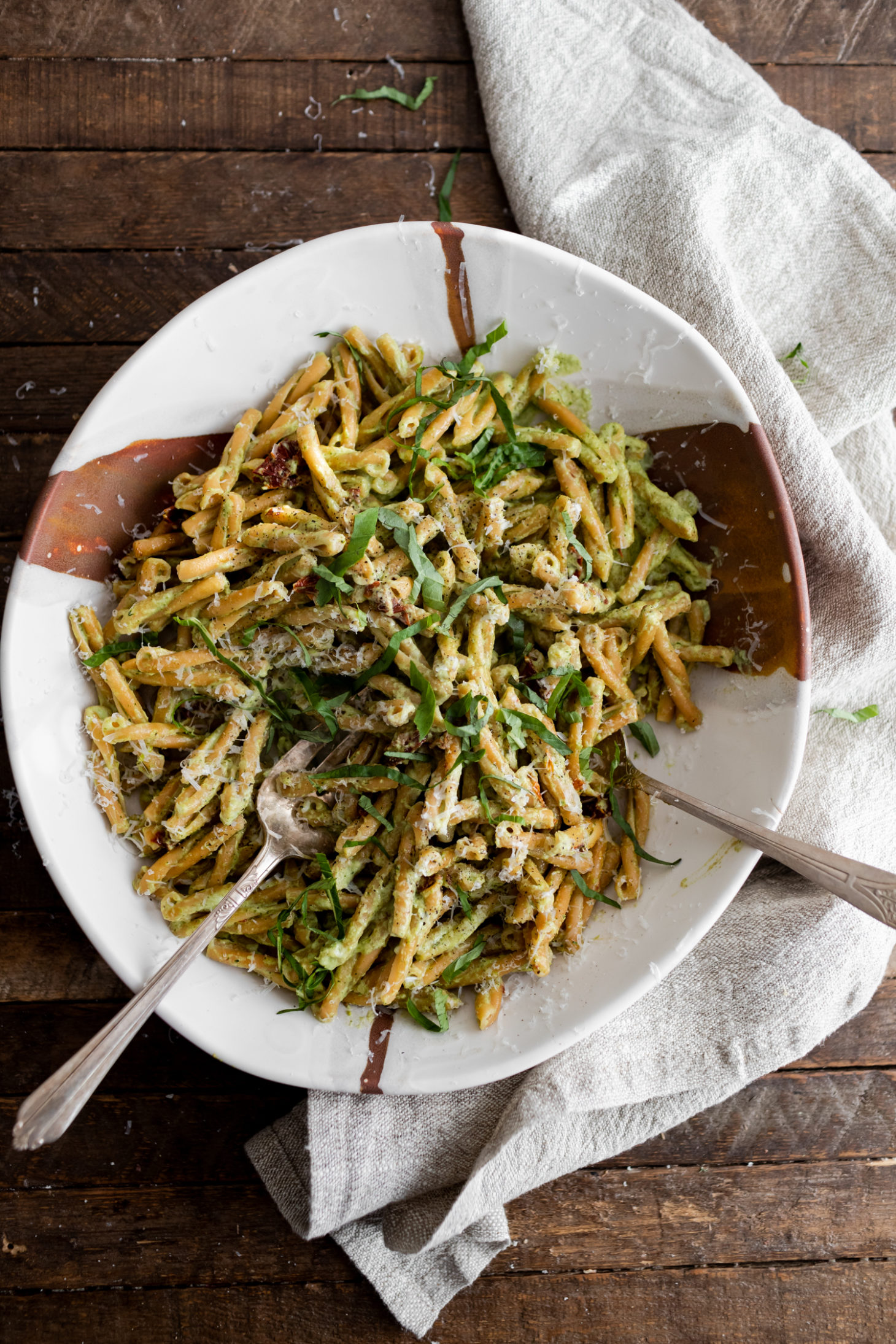 Photograph of a full, large white bowl of pasta tossed with a broccoli pesto.