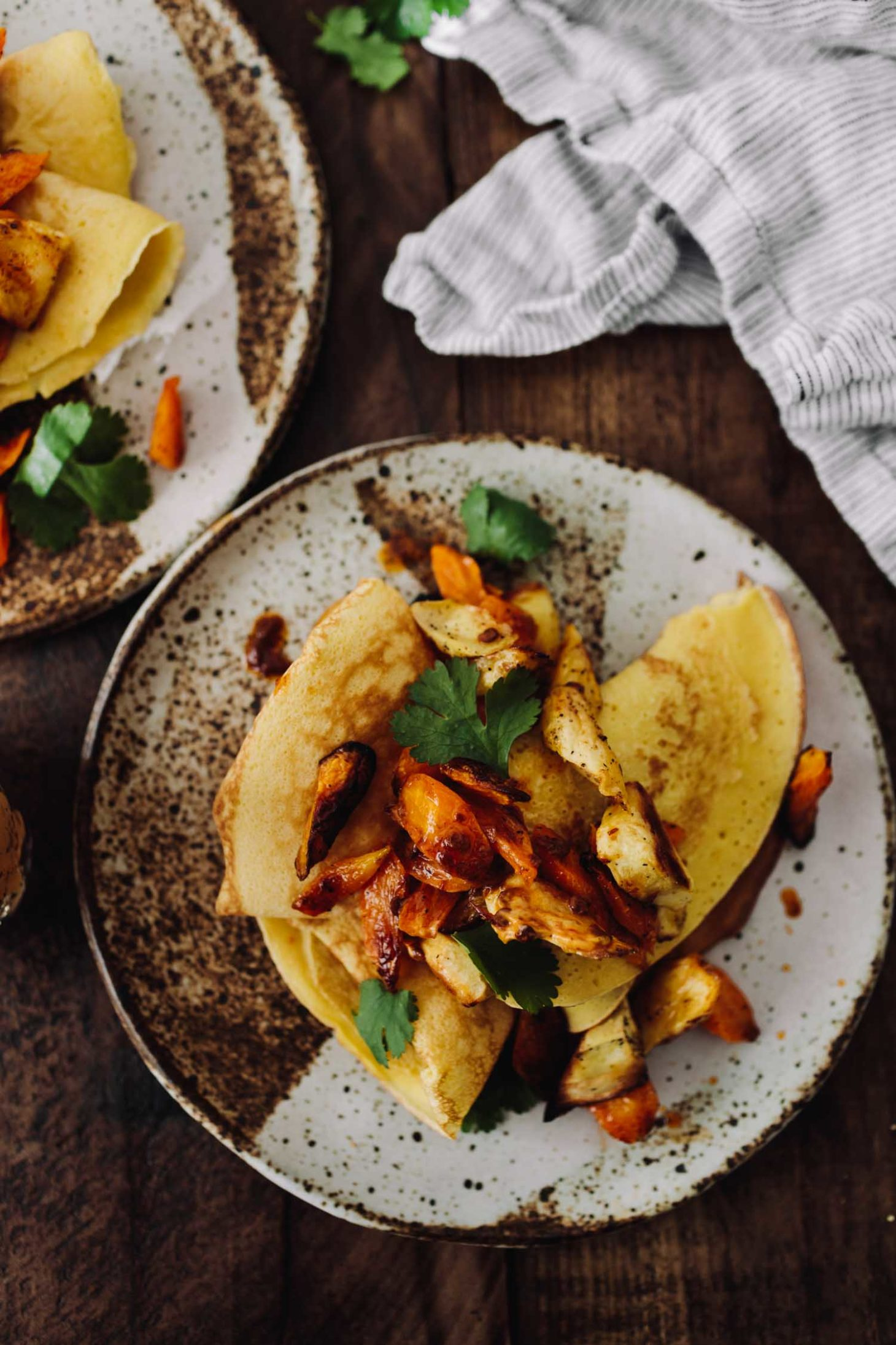 Overhead photo, close-up, of yellow chickpea crepes topped with parsnip and carrot pieces and chipotle compound butter