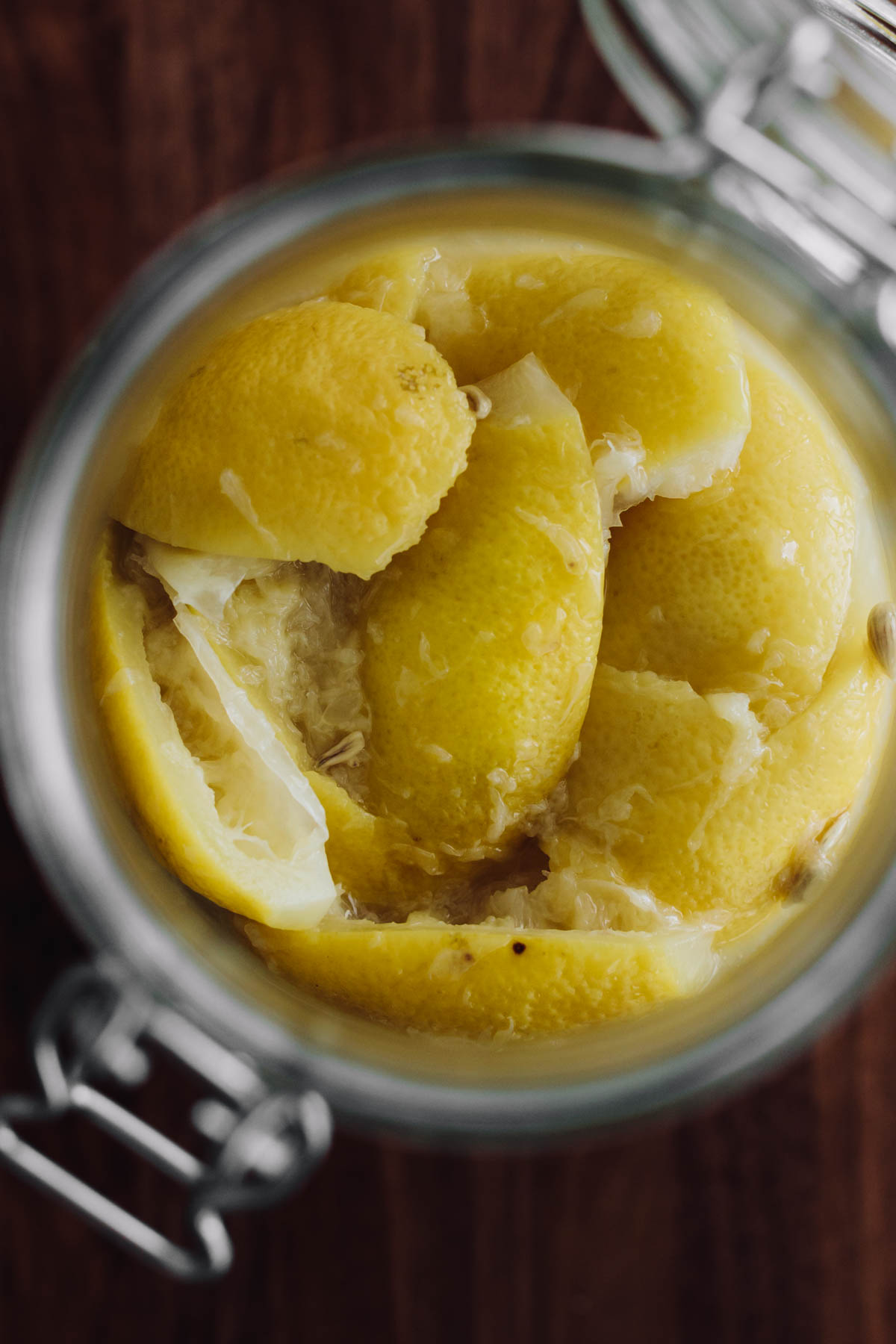 Close-up overhead photograph of lemons preserved in lemon juice and salt.