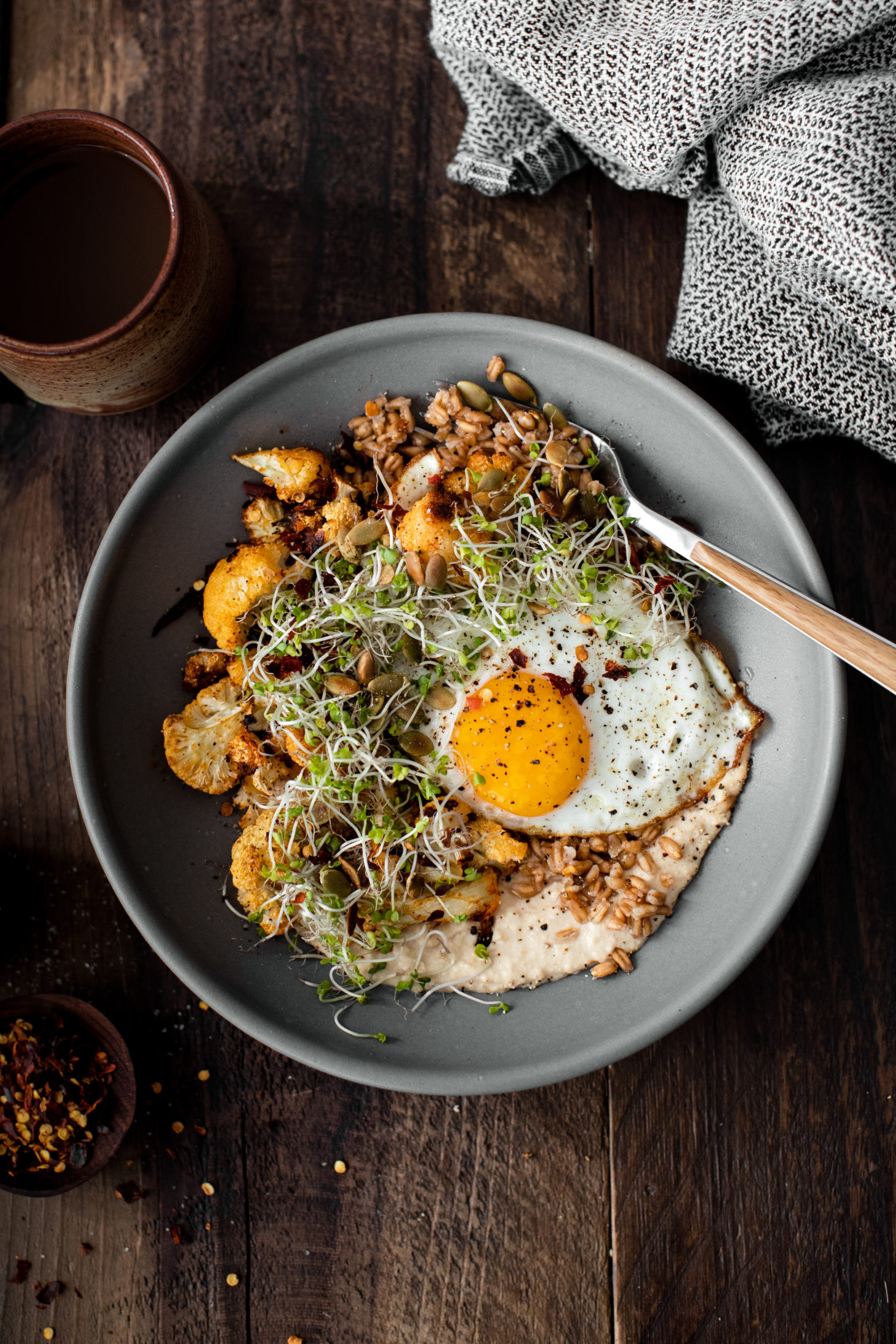 Overhead photograph of a grey bowl with fried egg on-top of paprika roasted cauliflower, farro, and hummus.