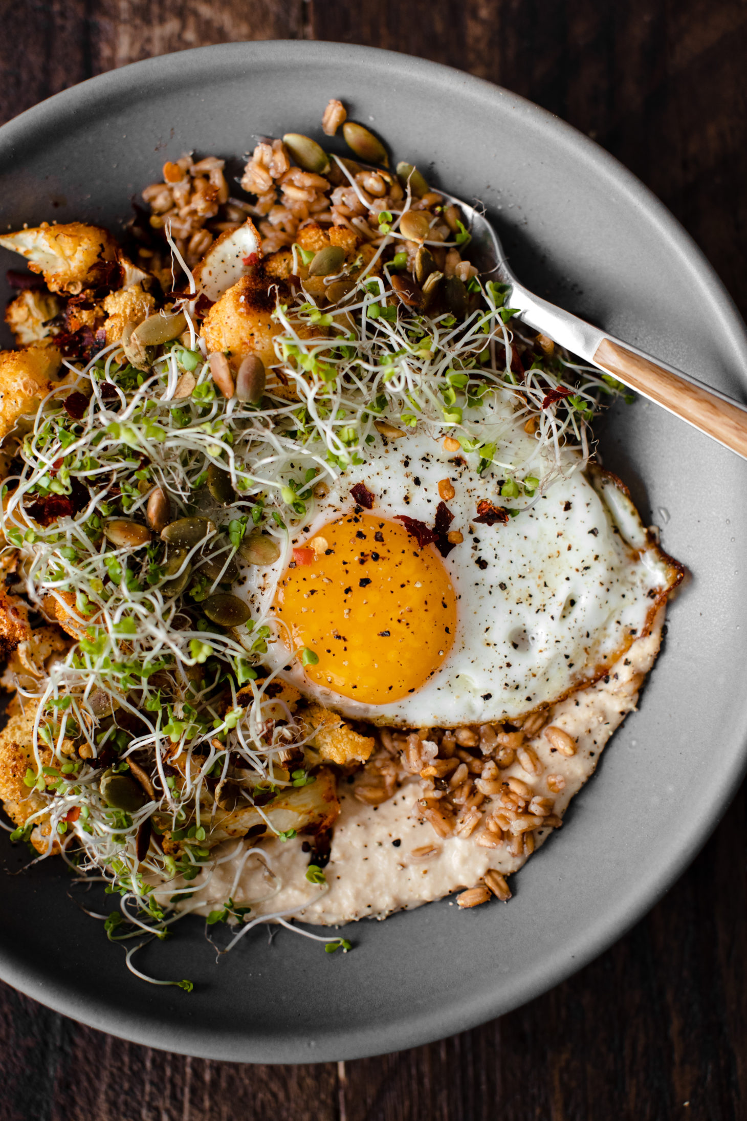 Close-up overhead photograph of a grey bowl with farro, hummus, roasted cauliflower, and a fried egg.