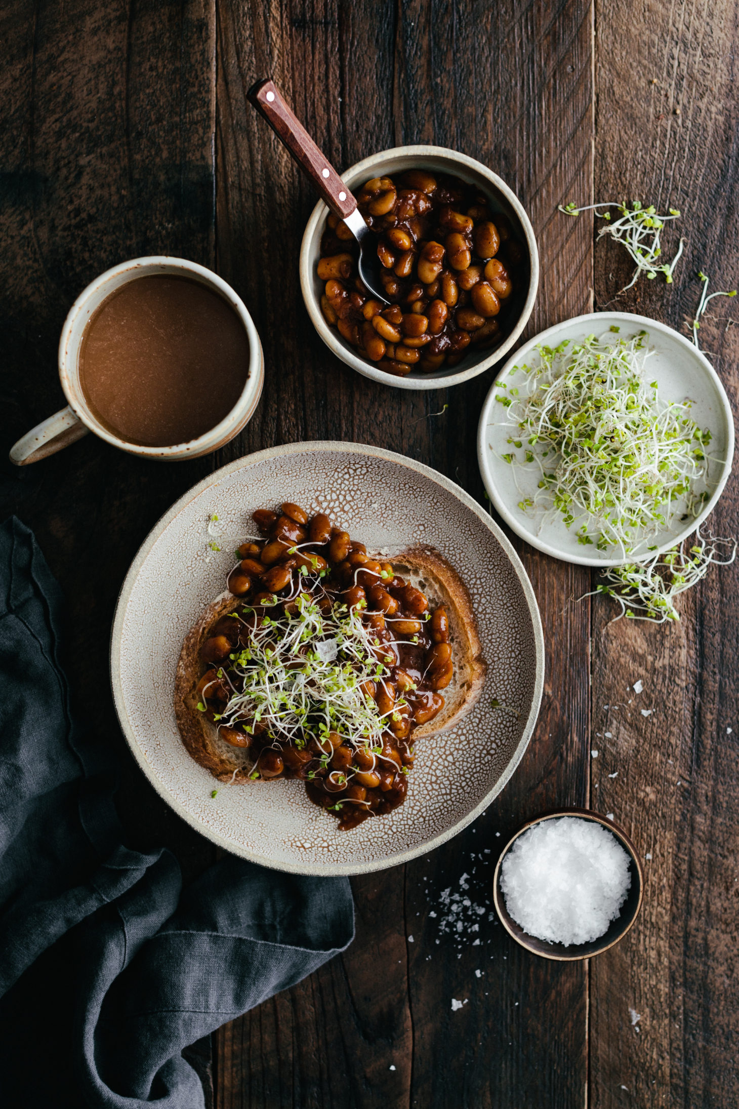 Overhead photo of a piece of toast topped with vegan baked beans and broccoli microgreens.