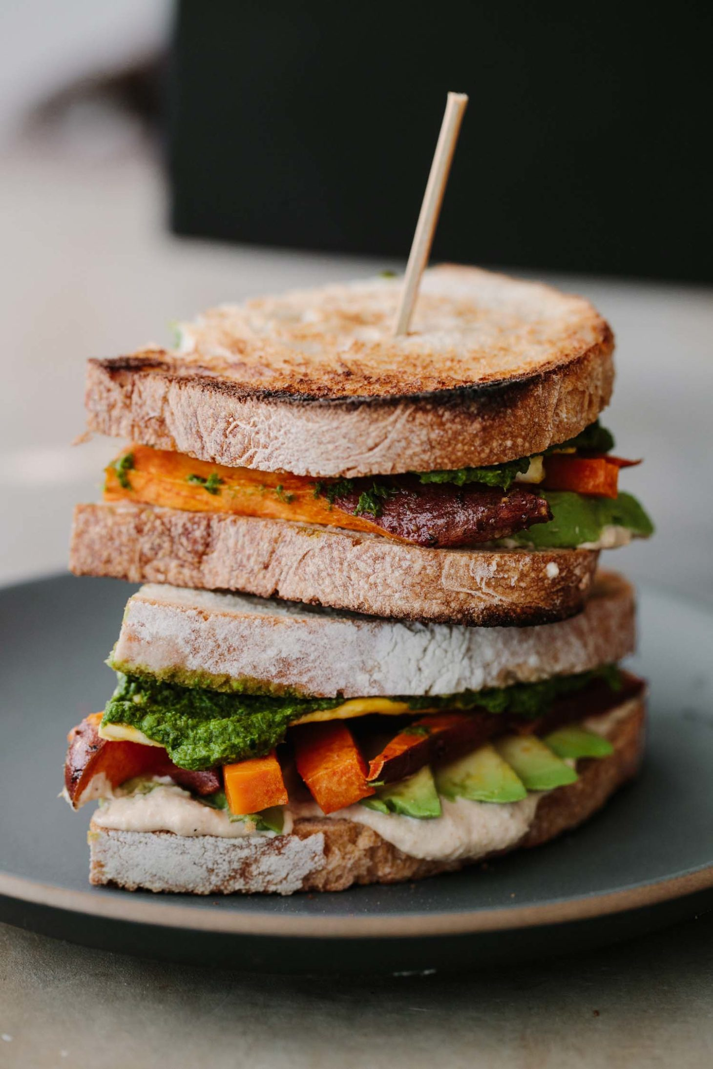 Side-angle photograph of sandwich cut in half and stacked on top of each other with hummus, sweet potato, avocado, and eggs.