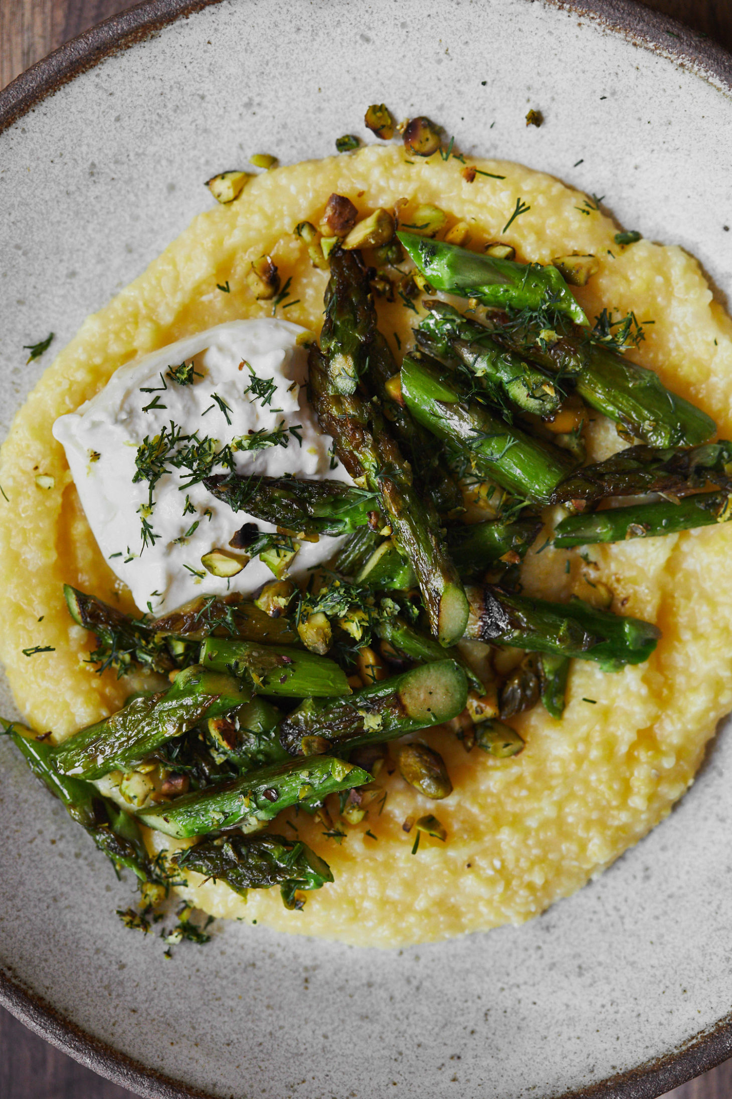 Close-up of asparagus polenta with burrata and a pistachio-dill mix.