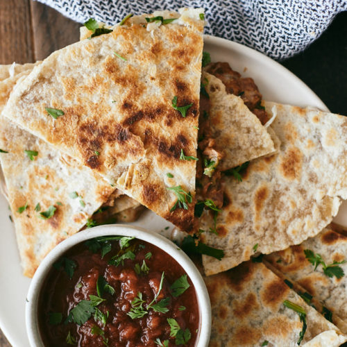 Overhead photograph of quesadillas on a white plate with a small white bowl of red salsa.
