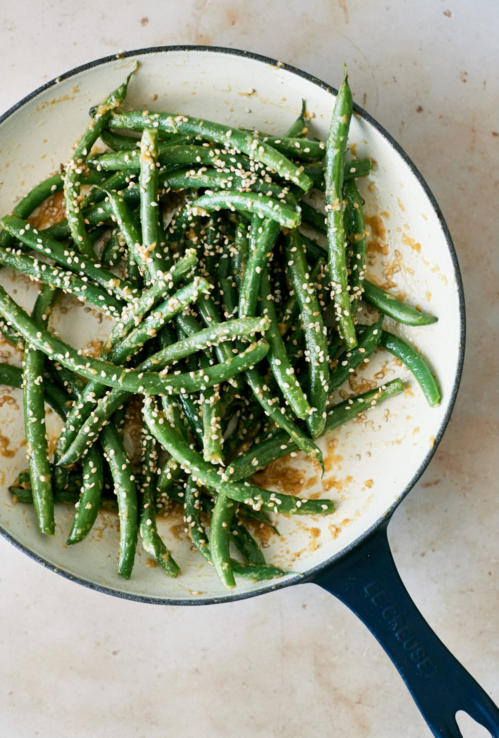 Overhead photo of green beans in a white enamel pan.