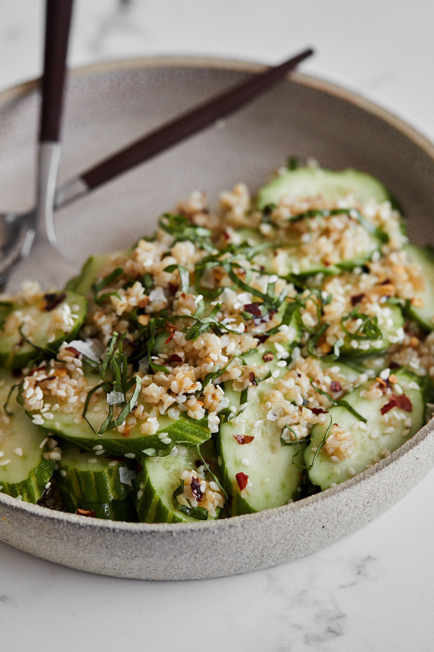 Close-up, side angle photograph of a cucumber salad tossed with bulgur and sesame seeds.
