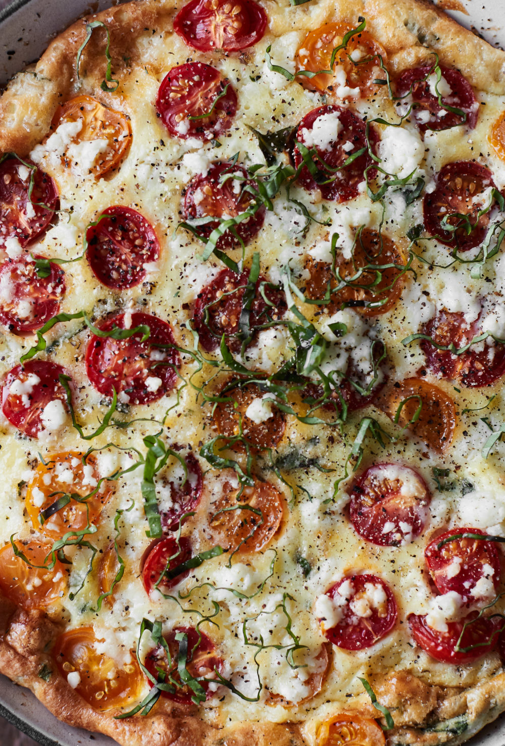 Close-up photograph of a frittata with cherry tomatoes, bulgur, and feta.