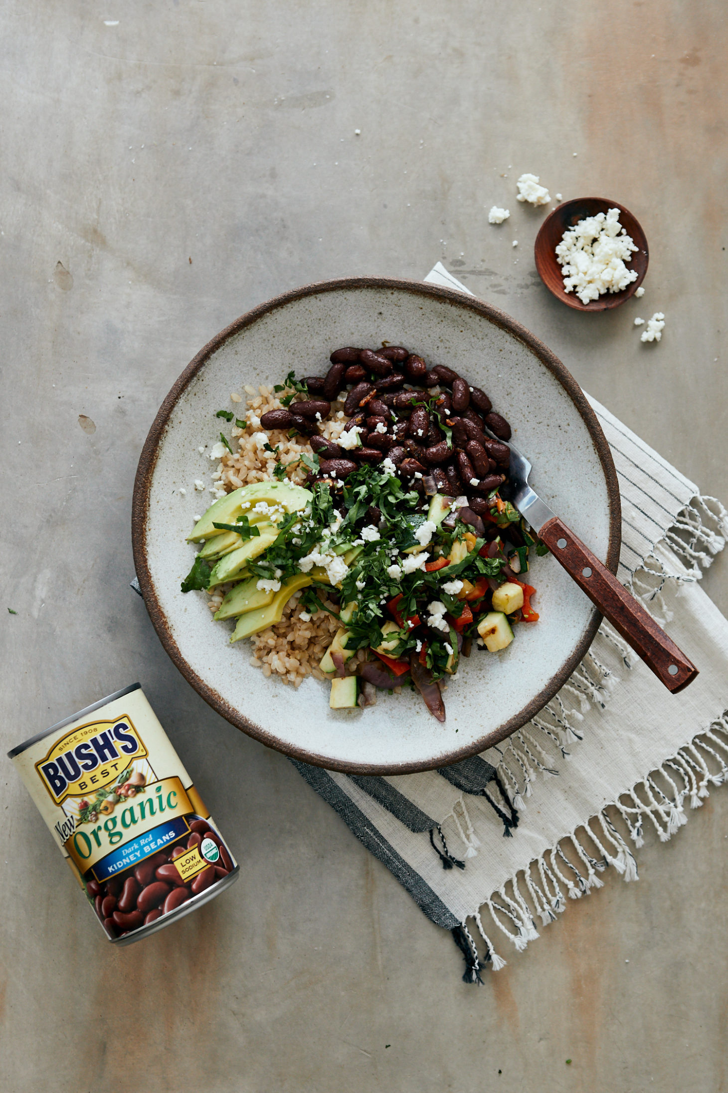 Light grey background with a small bowl of crumbled cheese and a large bowl filled with brown rice, grilled vegetables, kidney beans, and avocado.