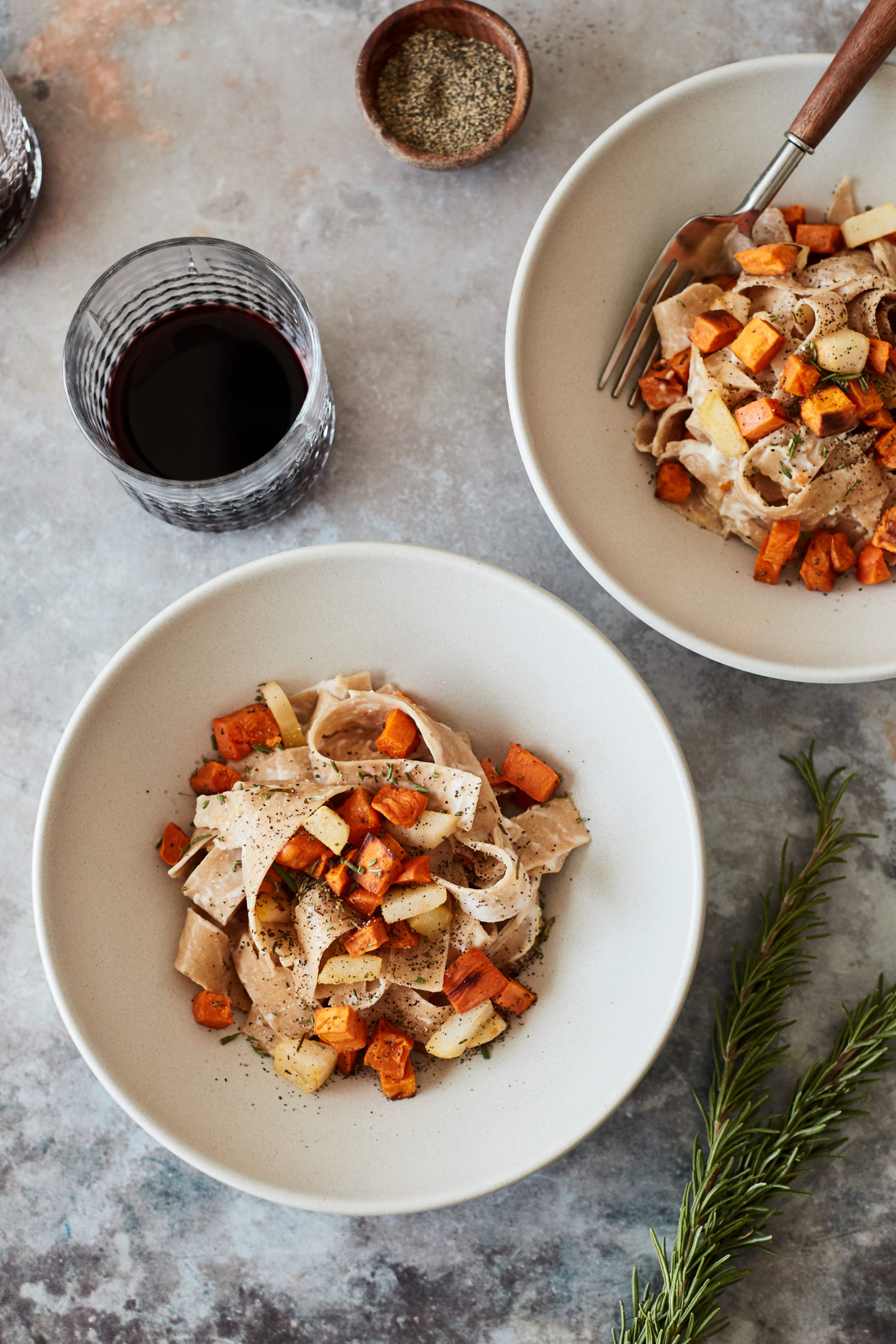 Image of two bowls of pasta with roasted orange sweet potato and a glass of red wine.