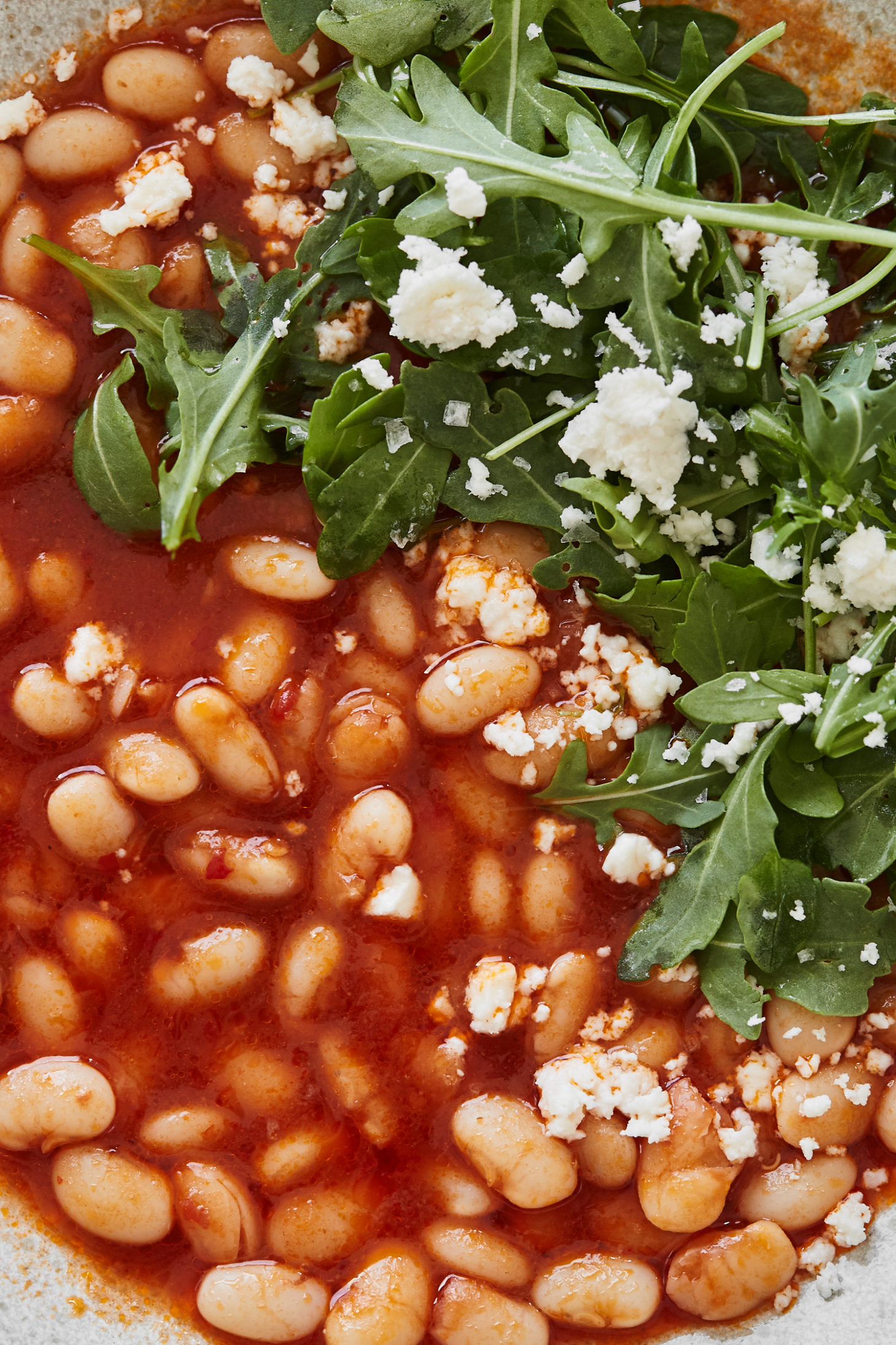 Close-up image of white beans in a tomato broth with arugula and feta on top.