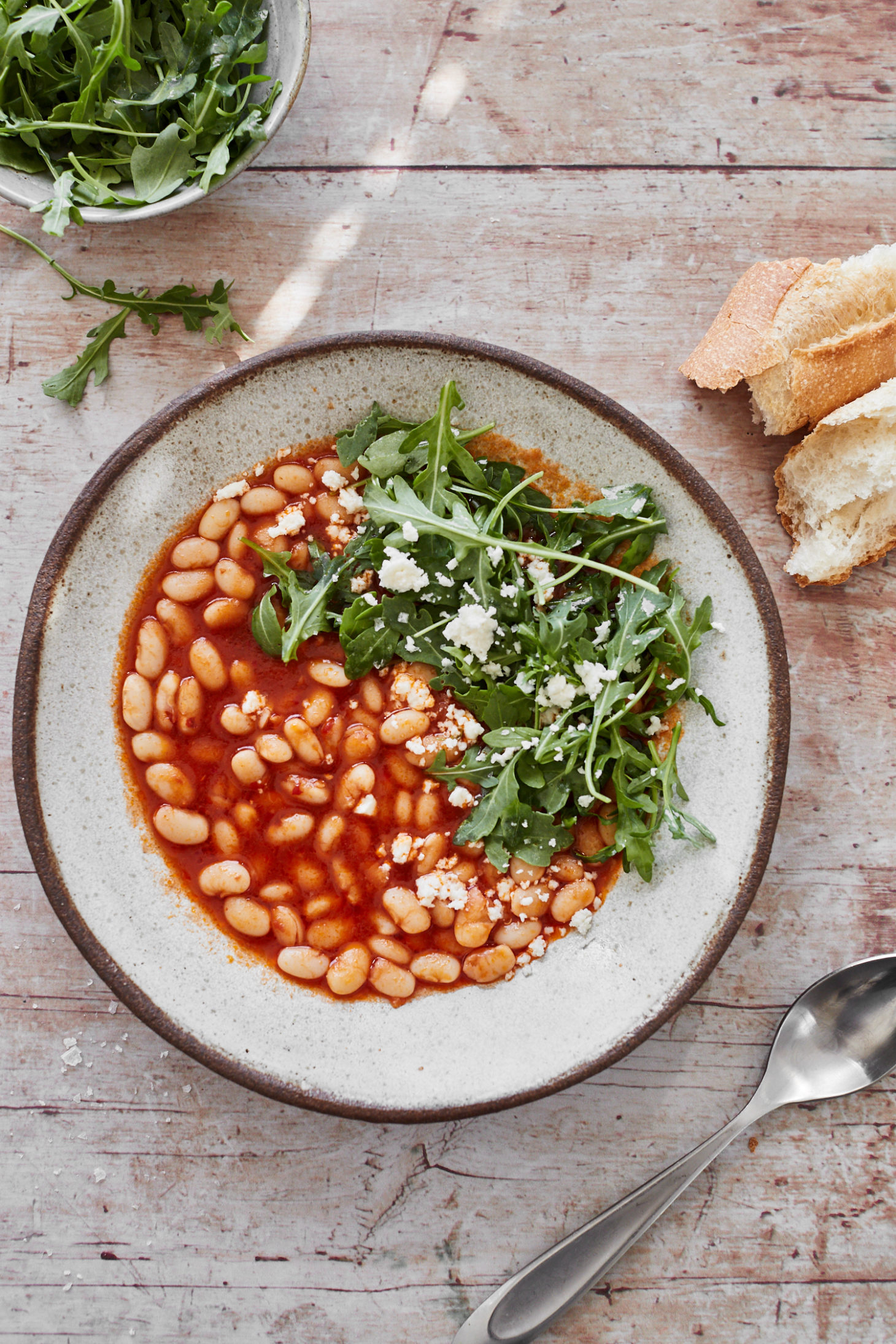 Light image with a bowl of tomato bean stew with arugula on top on a white background.