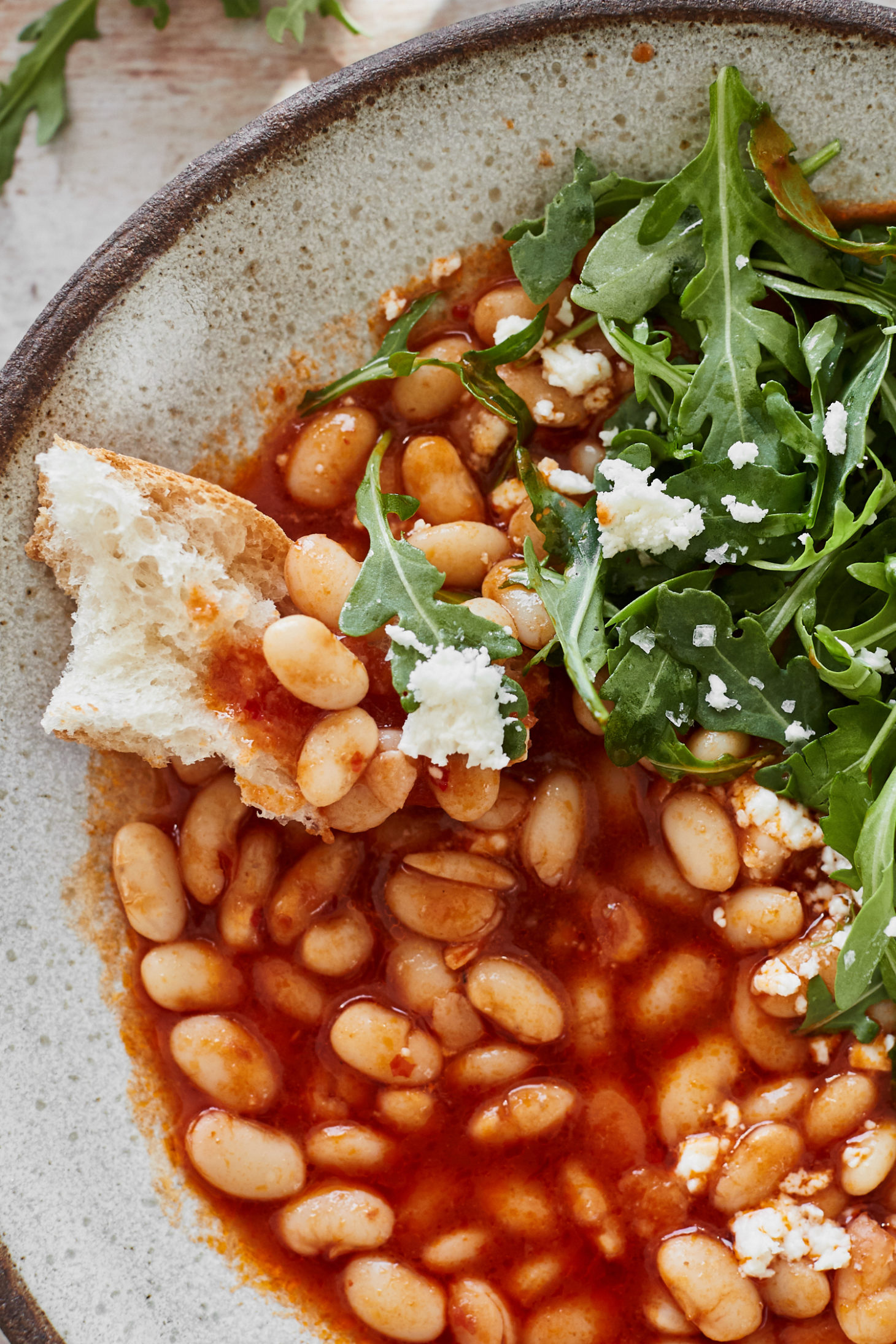 Close-up image of a piece of bread topped with beans in a red broth.