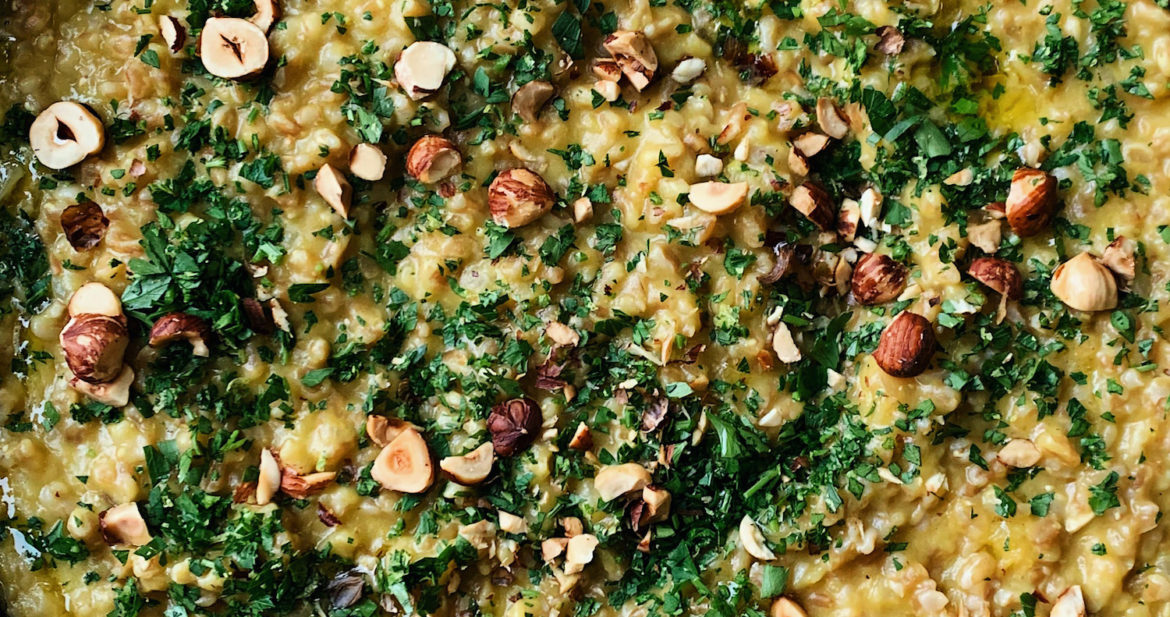 Close-up photograph of farro risotto with acorn squash puree and topped with toasted hazelnuts and gremolata