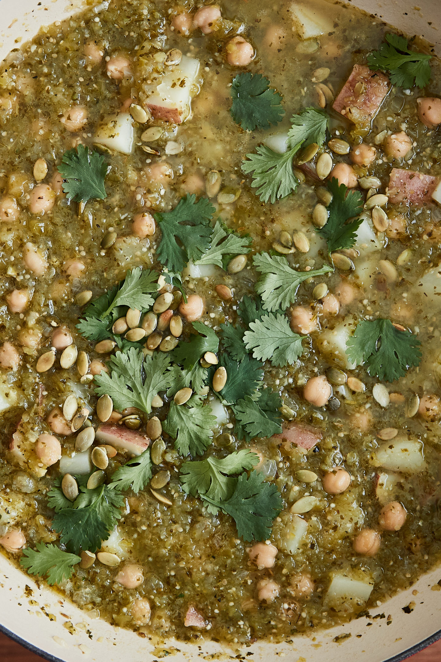 A close-up photo of green chickpea chili topped with cilantro and pepitas.