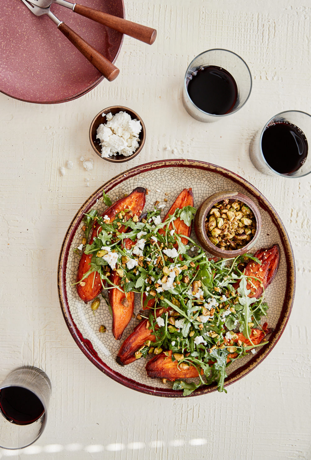 overhead image of sweet potatoes covered with arugula on a crackled large plate