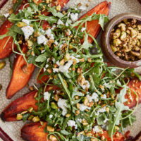a light crackled plate with sweet potatoes topped with arugula and pistachios