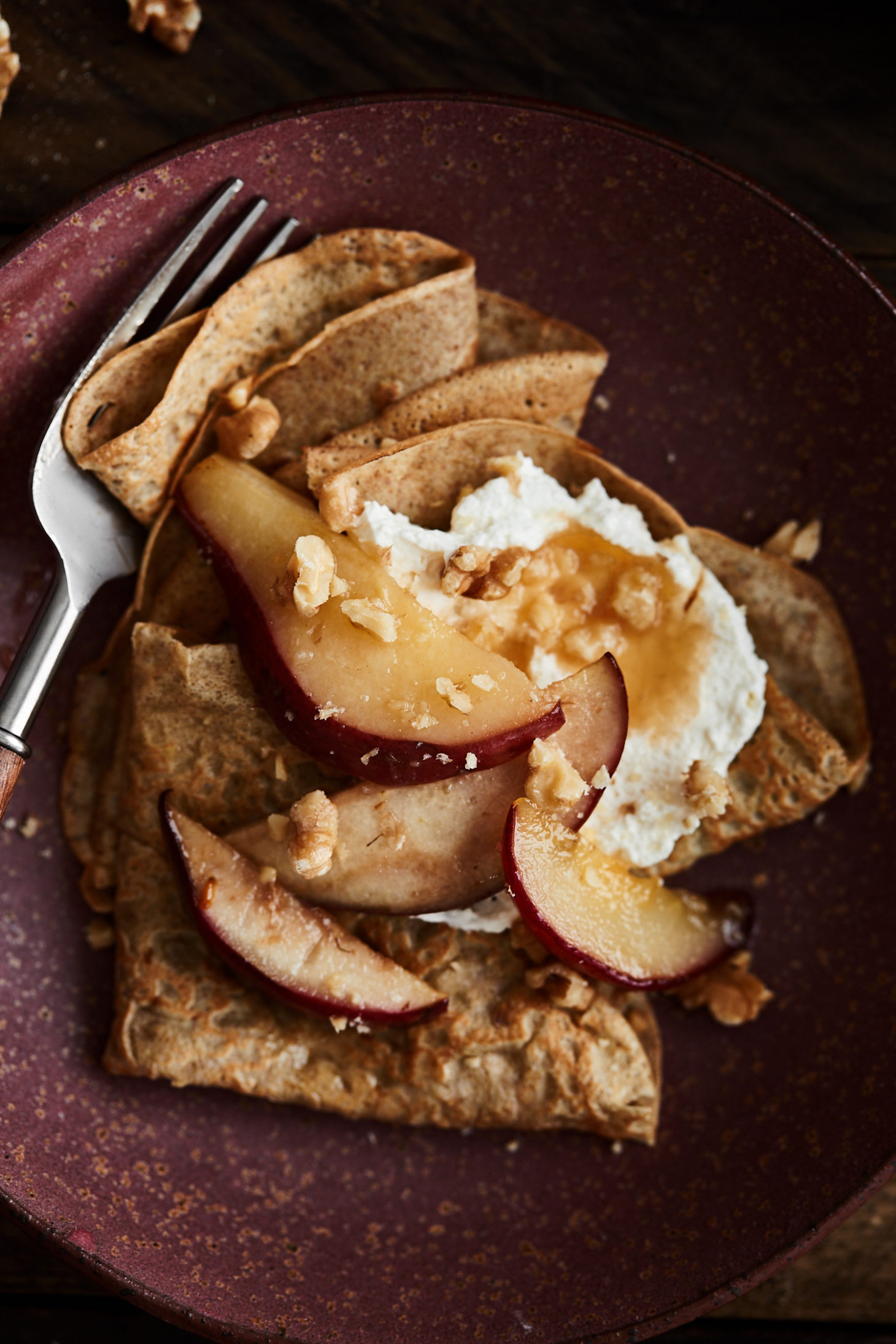 Close-up of rye crepes on a maroon plate topped with pears, whipped crepe, and walnuts.