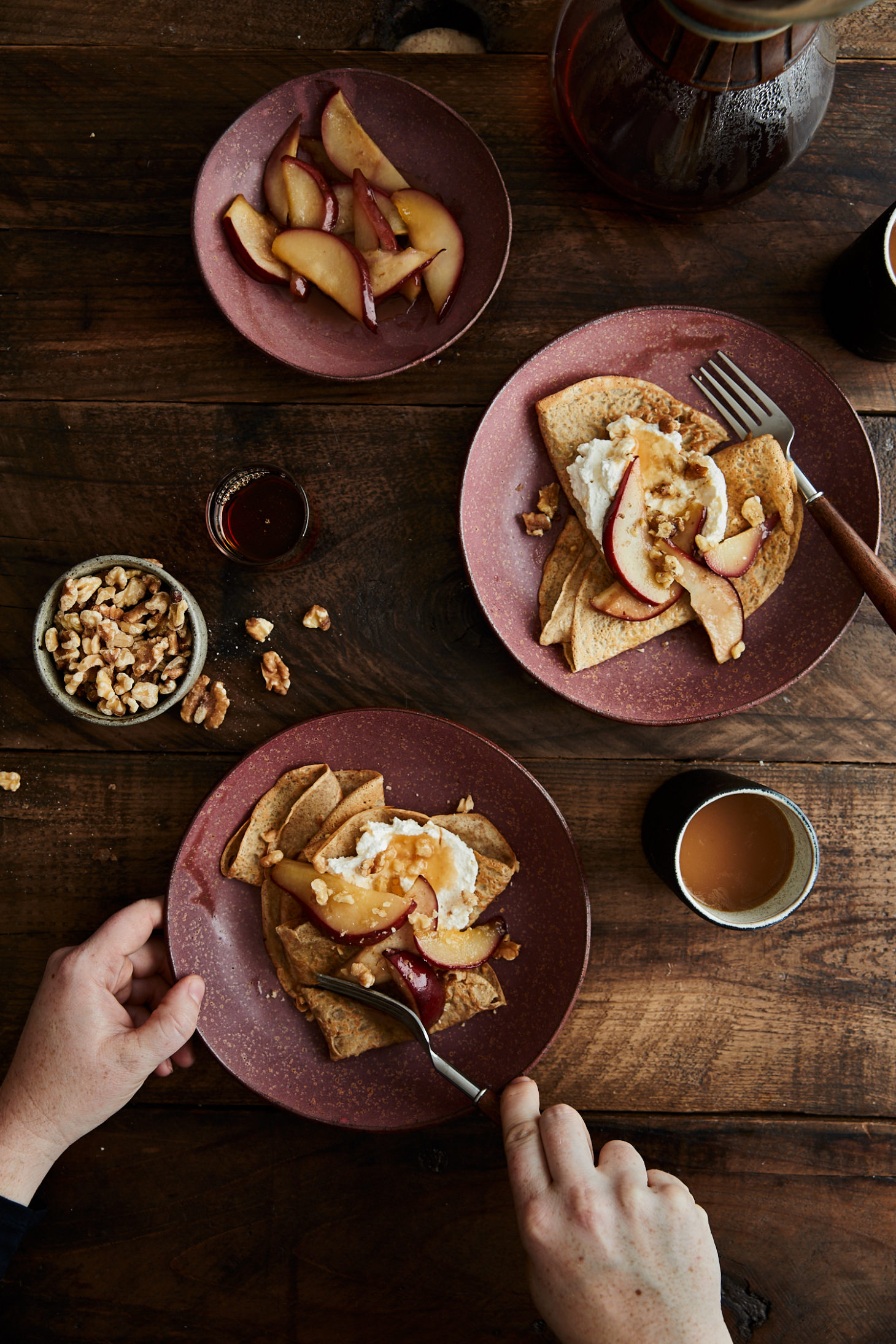 Image of two plates of crepes with pears and hands cutting into one of the crepes.