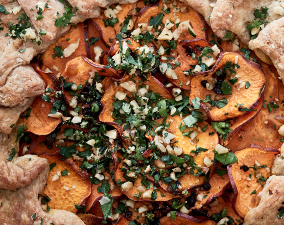 Close-up image of a whole wheat galette with sweet potatoes on a blue plate.