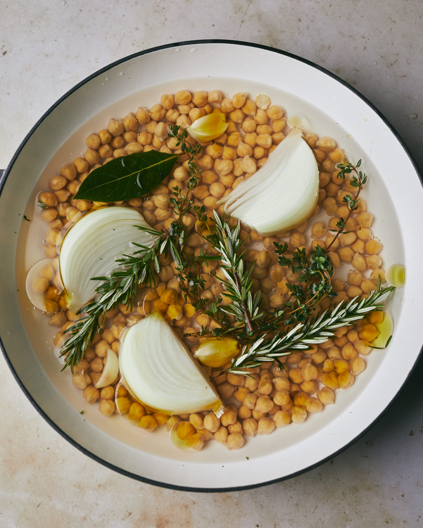 Close-up photo of soaked beans in a pot with herbs, onions, garlic, and olive oil