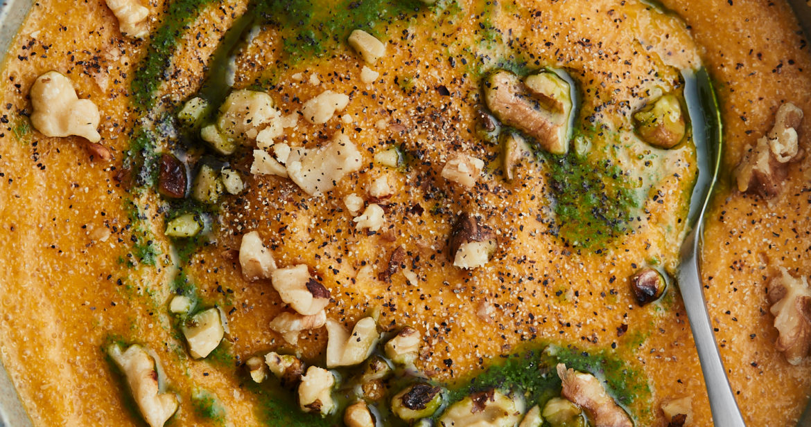 Close-up image of amaranth polenta with carrot puree and topped with parsley oil and walnuts.