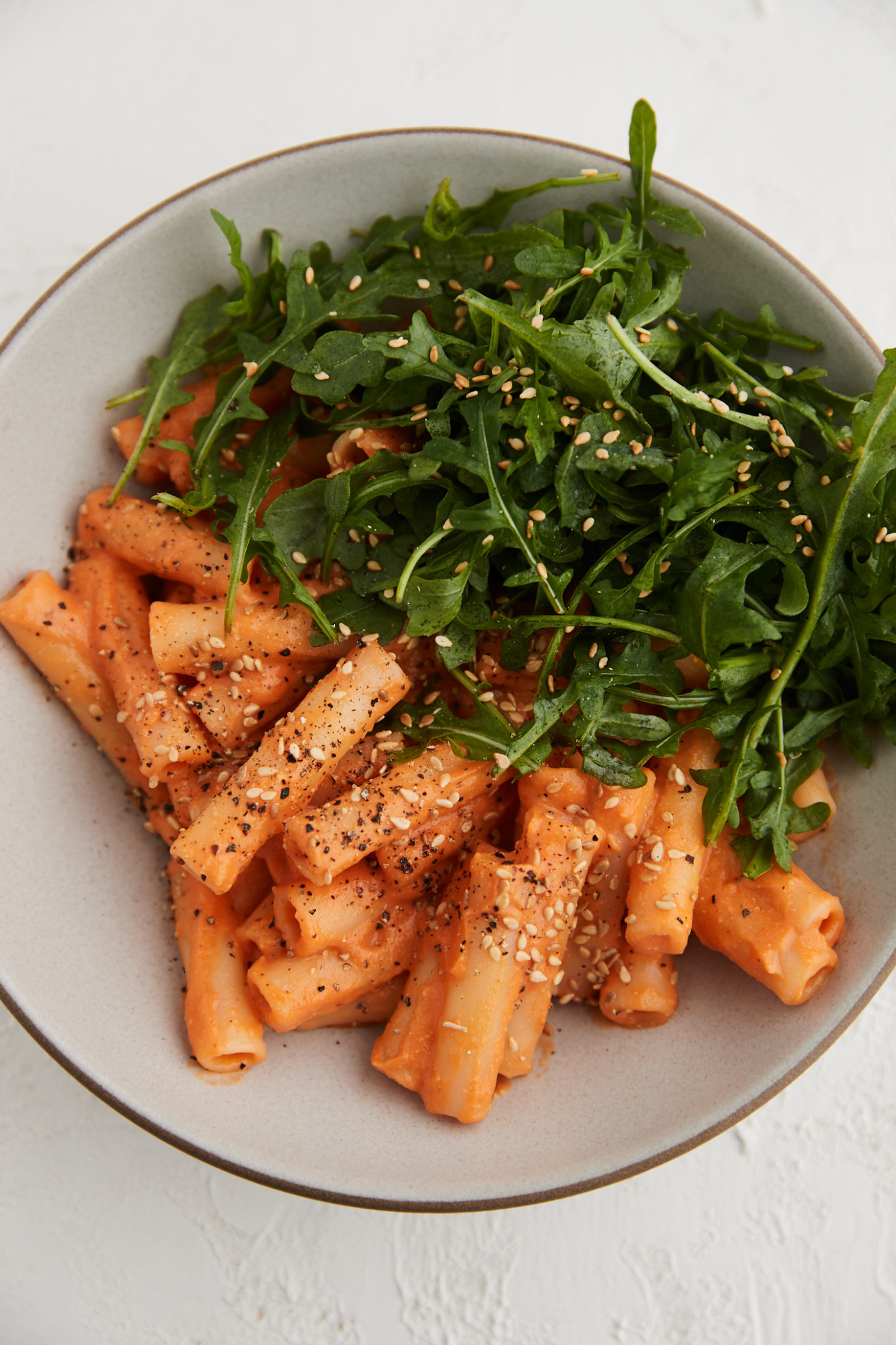 Close-up image of pasta topped in a carrot sauce and arugula.