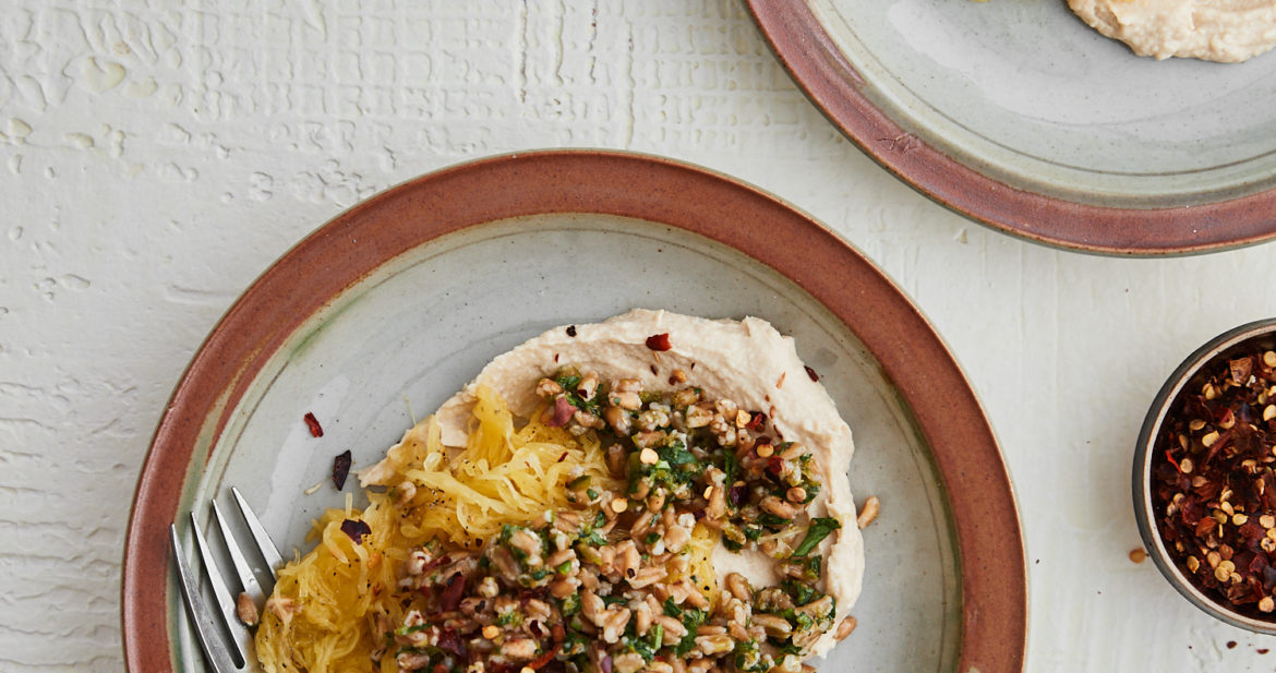A white background with two grey plates topped with hummus, farro, and spaghetti squash. Two smaller bowls with herbs and crushed red peppers.