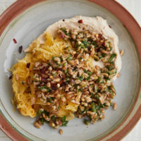 A grey plate with brown rim topped with hummus, spaghetti squash, and farro.