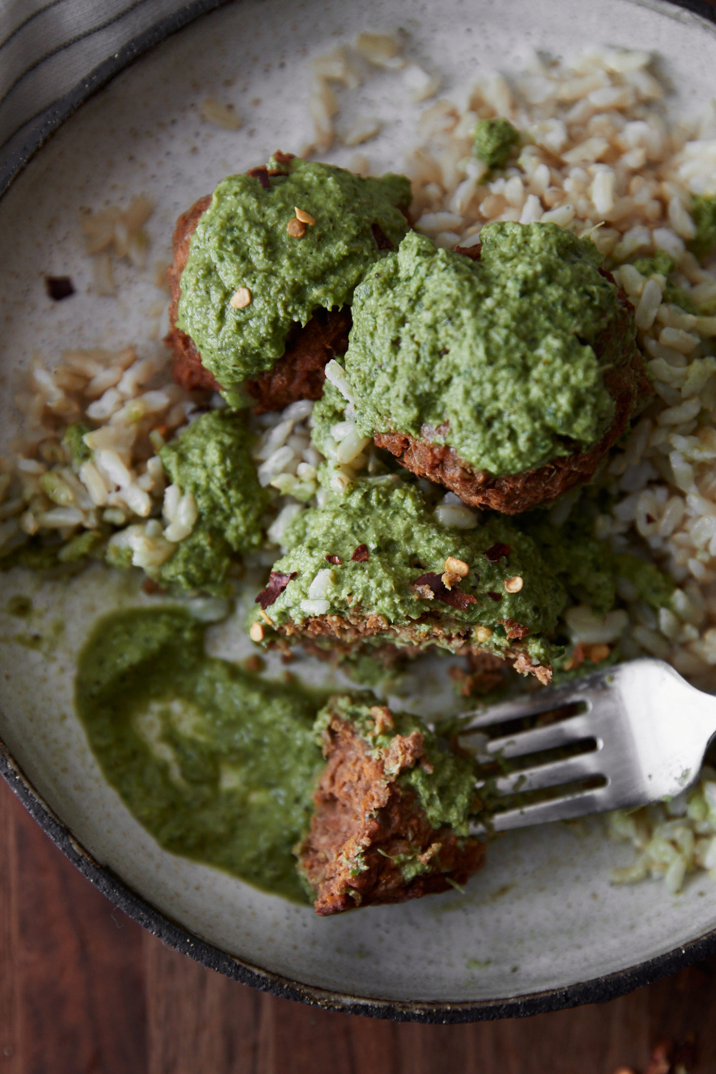 close-up of a cream bowl with green broccoli pesto with lentil bites and rice.