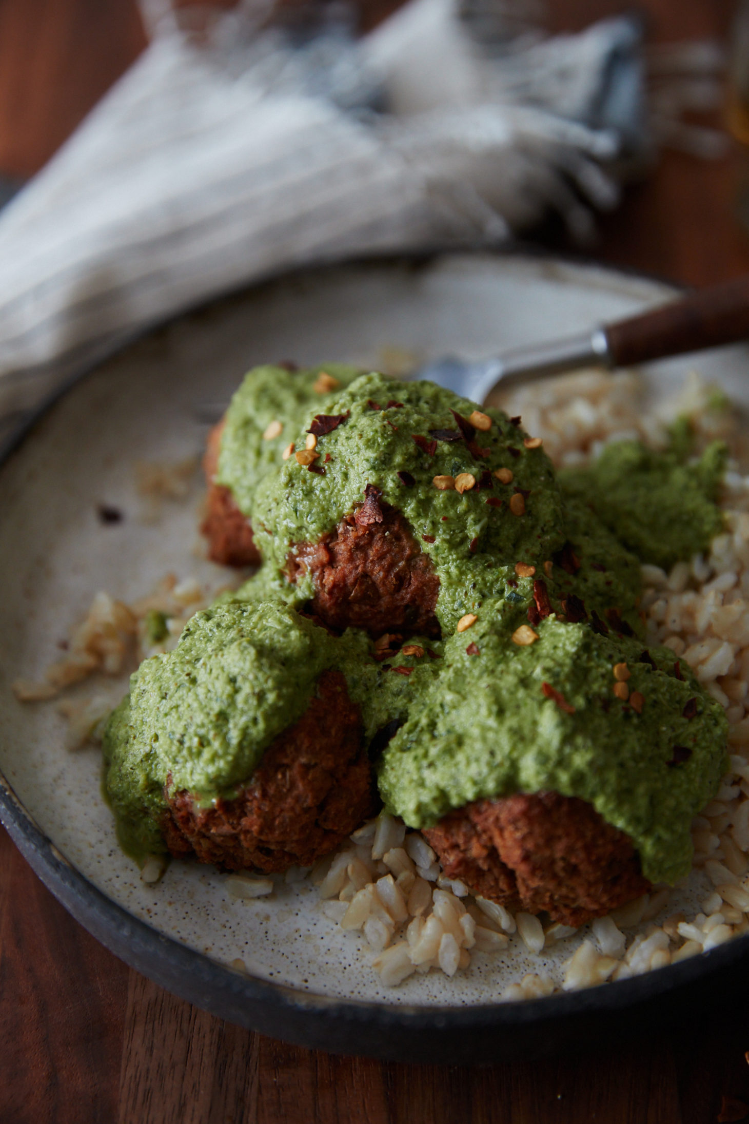 Side-angle photo of a cream bowl with homemade lentil bites with rice and a green broccoli pesto.