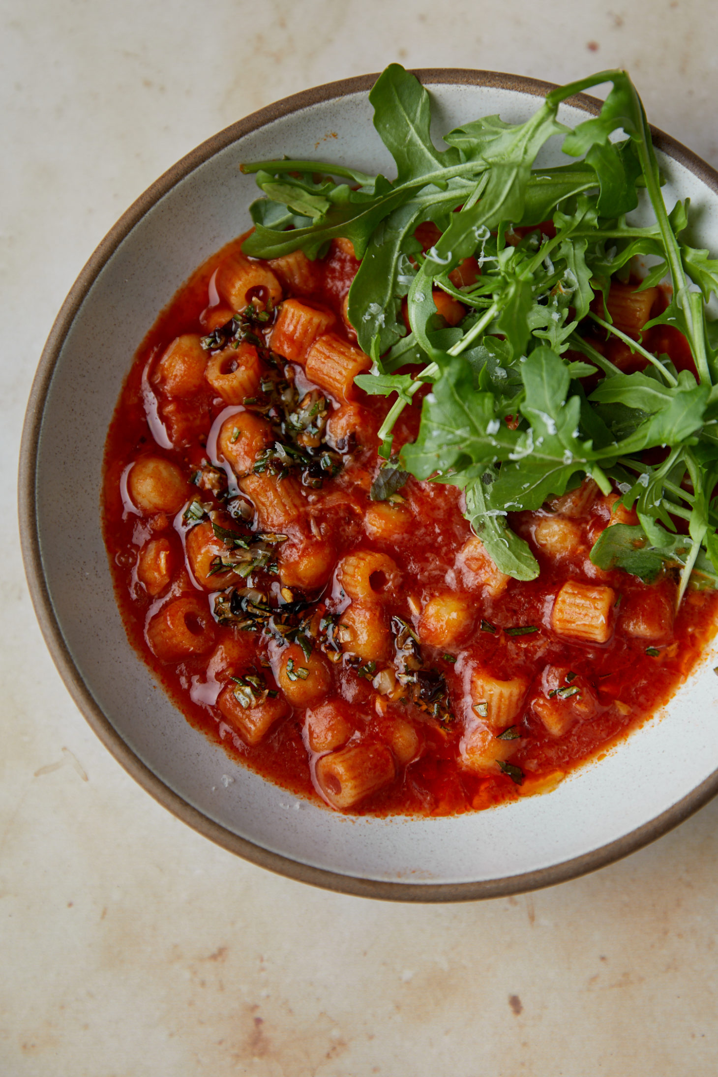 Close-up photo of a greyish bowl filled with pasta, chickpea, and tomato soup with arugula on top.